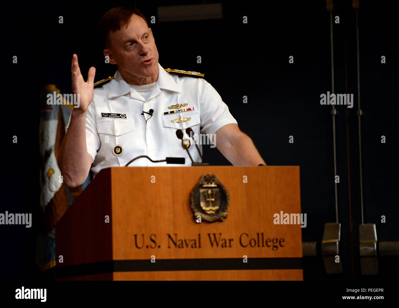 Adm. Michael S. Rogers, commander, U.S. Cyber Command, director, National Security Agency, chief, Central Security Service, provides a keynote address to students, staff, faculty and guests during a convocation ceremony kicking-off the 2015-2016 school year at NWC in Nepwort, Rhode Island. During the ceremony, Rogers provided a keynote address and was presented NWC's 2015 Distinguished Graduate Leadership Award.  The award honors NWC graduates who have earned positions of prominence in the national defense field.  (U.S. Navy photo by Chief Mass Communication Specialist James E. Foehl/Released) - Stock Image