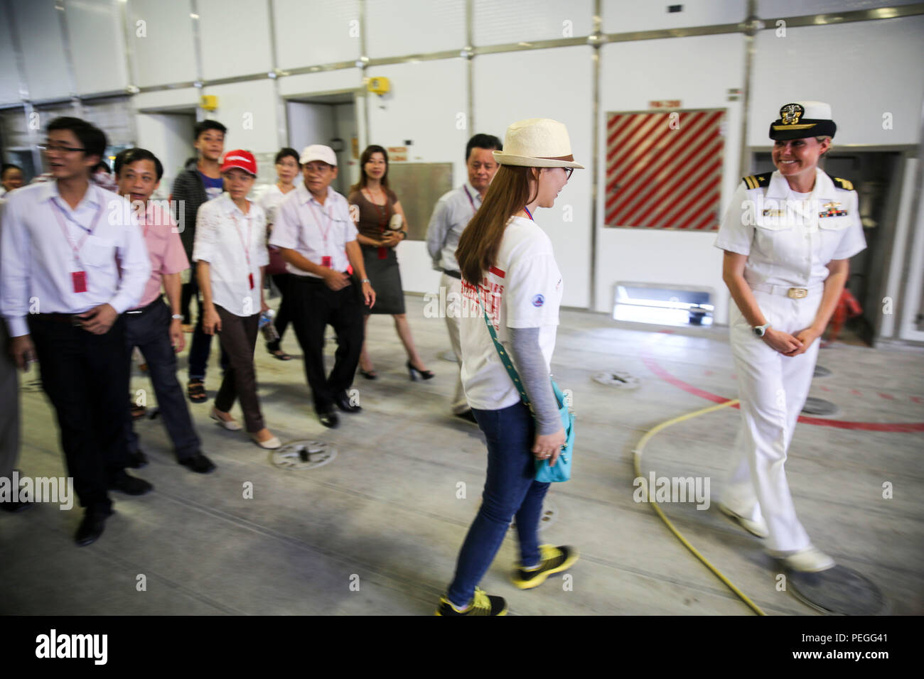 150820-M-GO800-013 DA NANG, Vietnam (Aug. 20, 2015) – Lt. Chelsea Irish leads local Vietnamese officials around the mission bay aboard the Military Sealift Command joint high speed vessel USNS Millinocket (JHSV 3) during a ship tour Aug. 20. Task Force Forager, embarked aboard the Millinocket  is serving as the secondary platform for Pacific Partnership, led by an expeditionary command element from the Navy's 30th Naval Construction Regiment (30 NCR) from Port Hueneme, Calif. Now in its 10th iteration, Pacific Partnership is the largest annual multilateral humanitarian assistance and disaster  - Stock Image