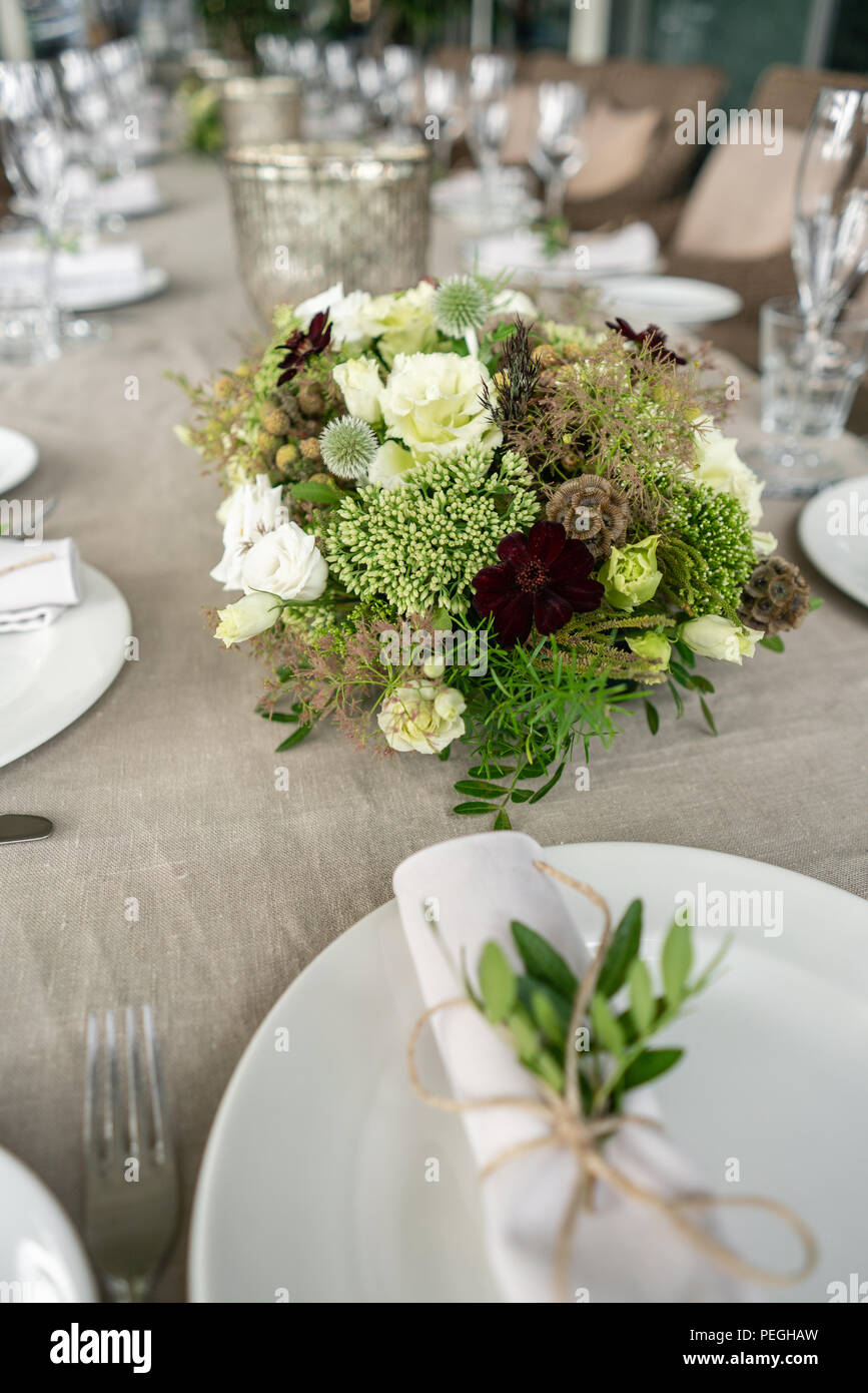 Neatly twisted into a tube dining room napkin decorated with a sprig of pistachio. Wedding Banquet or gala dinner. The chairs and table for guests, served with cutlery and crockery. party on terrace - Stock Image