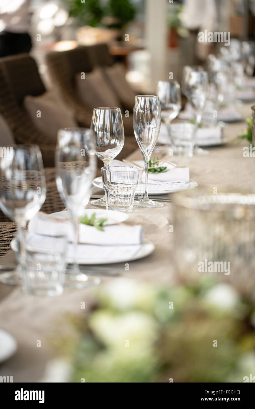 Wedding Banquet or gala dinner. The chairs and table for guests, served with cutlery and crockery. Covered with a linen tablecloth runner. party on terrace - Stock Image
