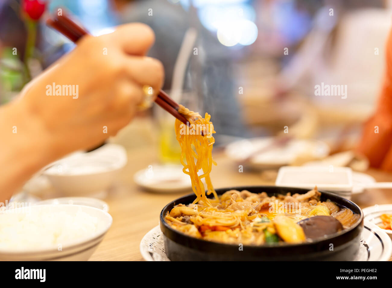 Hand with chopsticks eating Japanese udon noodles. - Stock Image