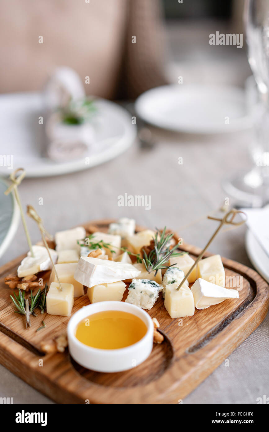 Cheese plate. Delicious cheese mix with walnuts, honey on wooden table. Tasting dish on a wooden plate. Food for wine. - Stock Image