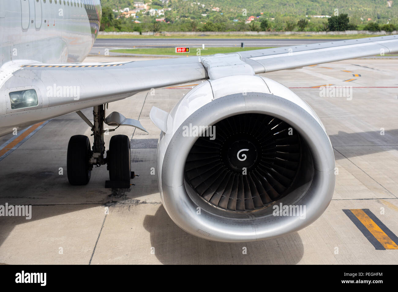 Turbine of 737-400 engine airplane in tropical airport background. - Stock Image