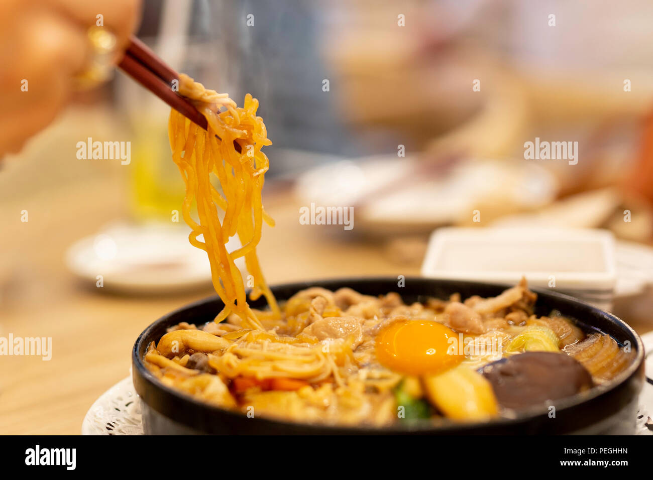 Hand with chopsticks eating Japanese udon noodles with egg. Stock Photo