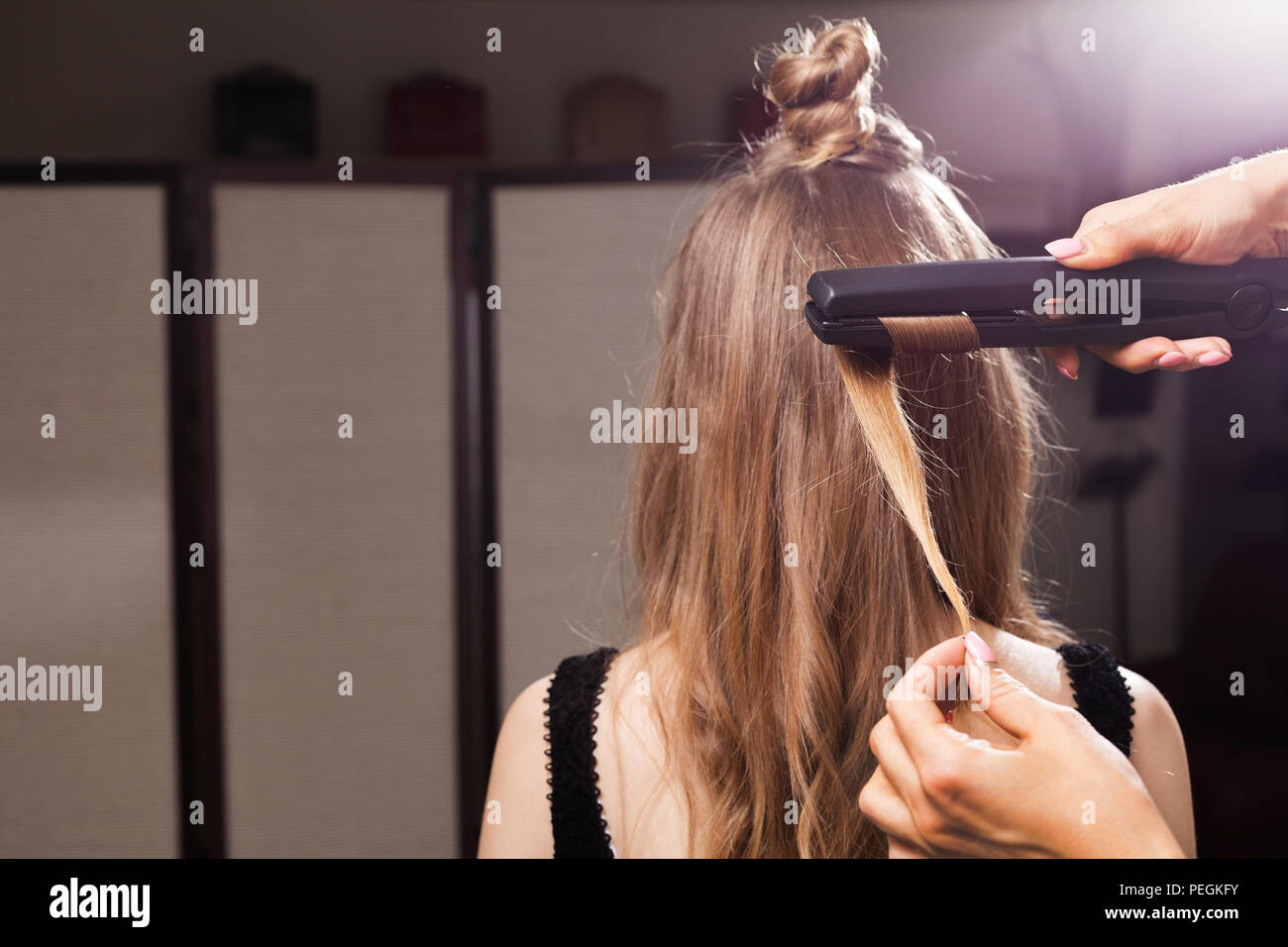 hairdresser curling a hair strand of a model - Stock Image