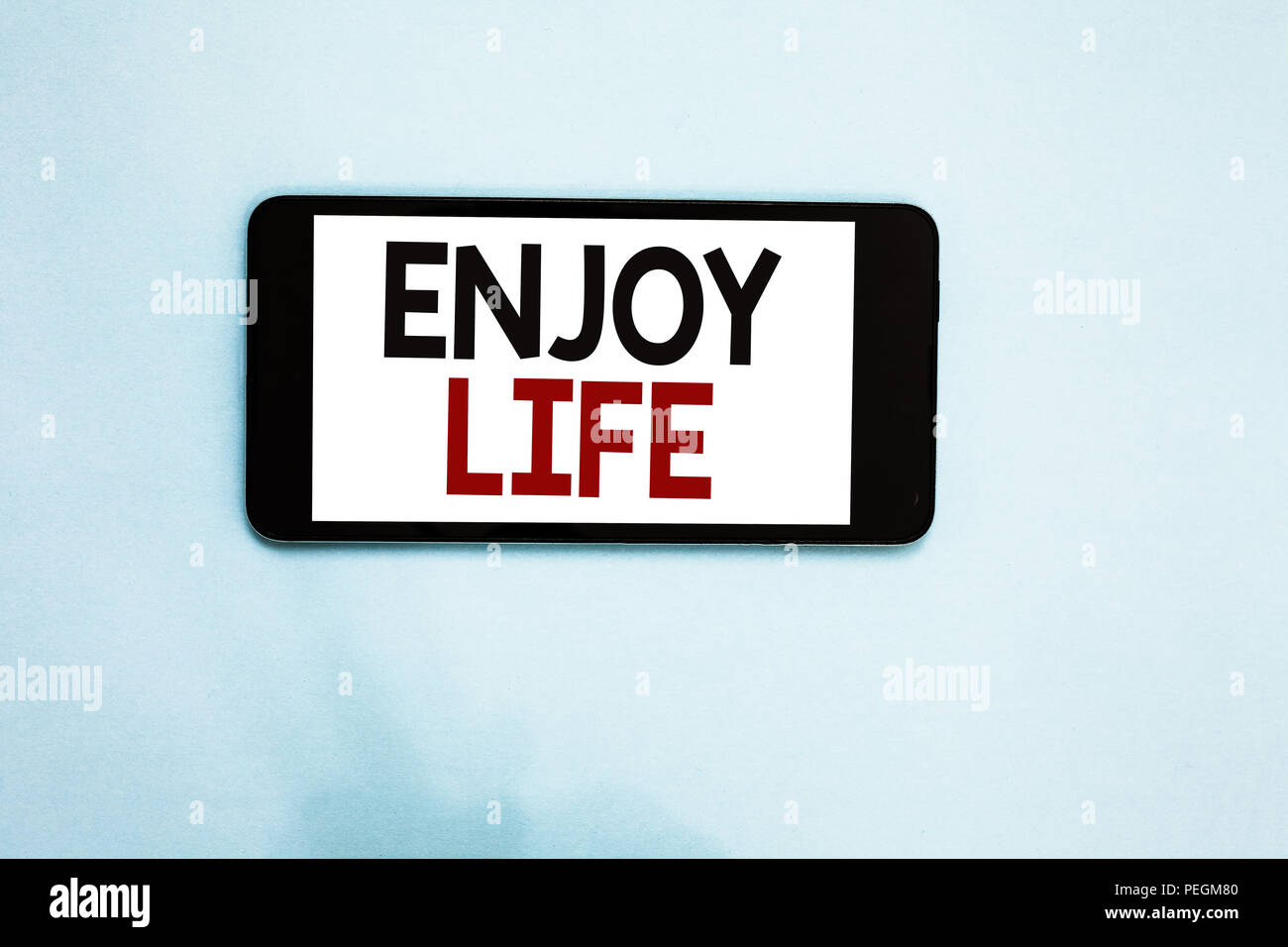 Text sign showing Enjoy Life. Conceptual photo Any thing, place,food or person, that makes you relax and happy Cell phone white screen over light blue - Stock Image