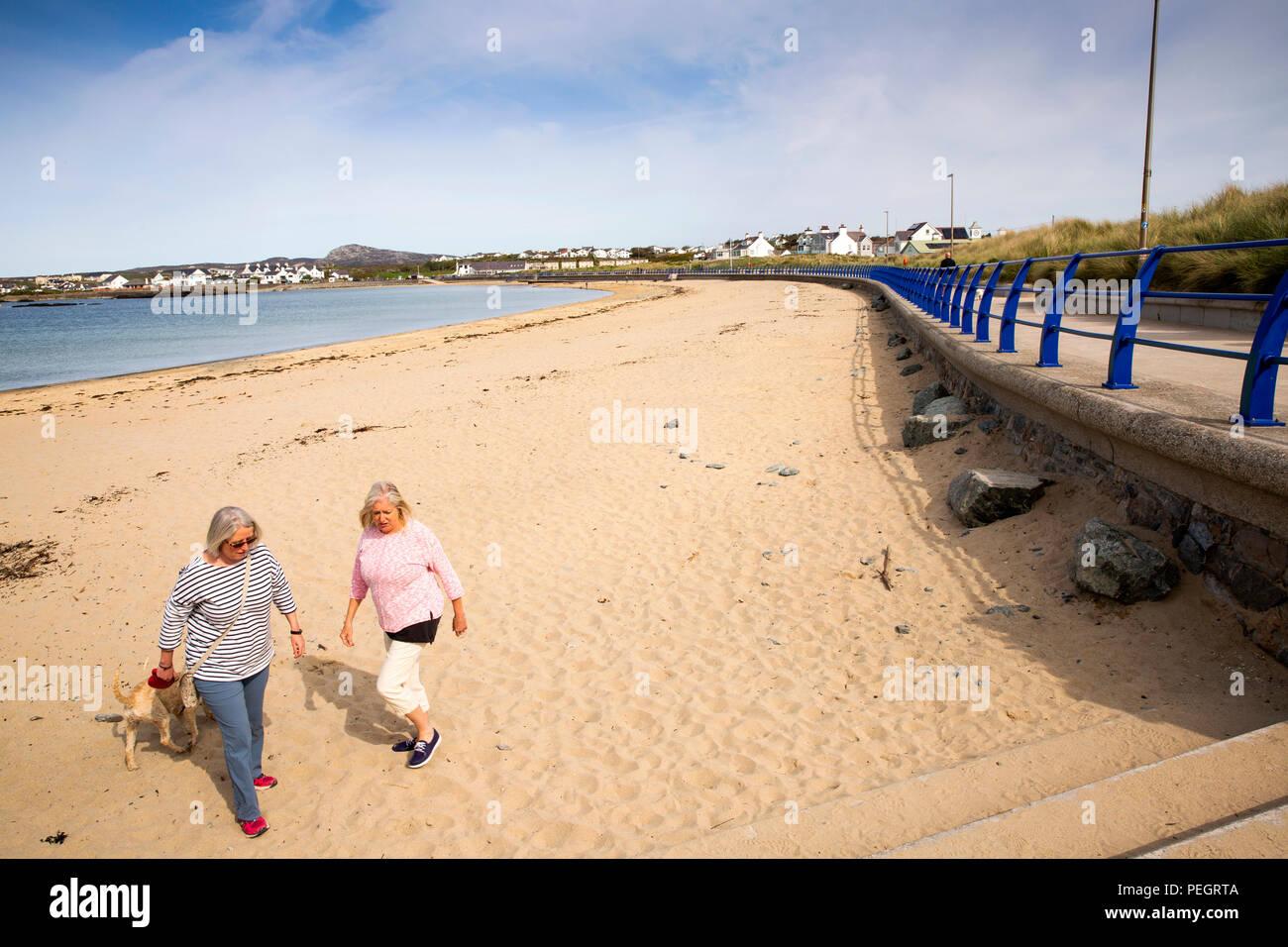 UK, Wales, Anglesey, Trearddur Bay, women dog walkers on beach in sunshine - Stock Image