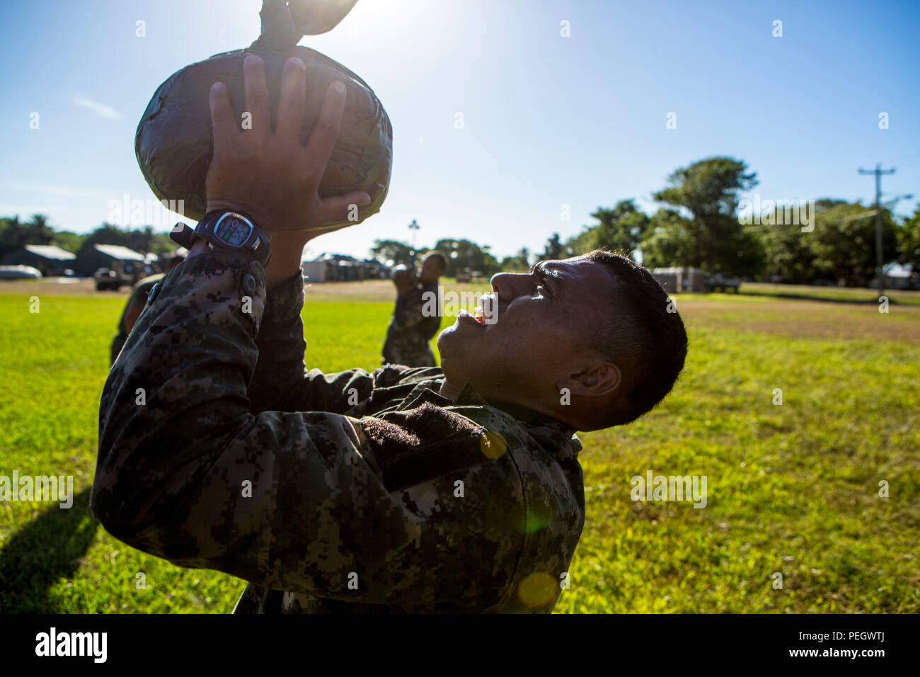 U.S. Marines with Security Cooperation Team-Honduras, Special Purpose Marine Air-Ground Task Force-Southern Command and Honduran marines participate in a physical training session at Naval Base Puerto Castilla, Honduras, Aug. 18, 2015. The session consisted of 200-meter sprints, sand bag presses, and culminated with a squad competition. SCT-Honduras is currently deployed as part of the SPMAGTF-SC to assist the Centro de Adiestramiento Naval with implementing a training curriculum to create a Honduran marine Program. (U.S. Marine Corps Photo by Cpl. Katelyn Hunter/Released) - Stock Image