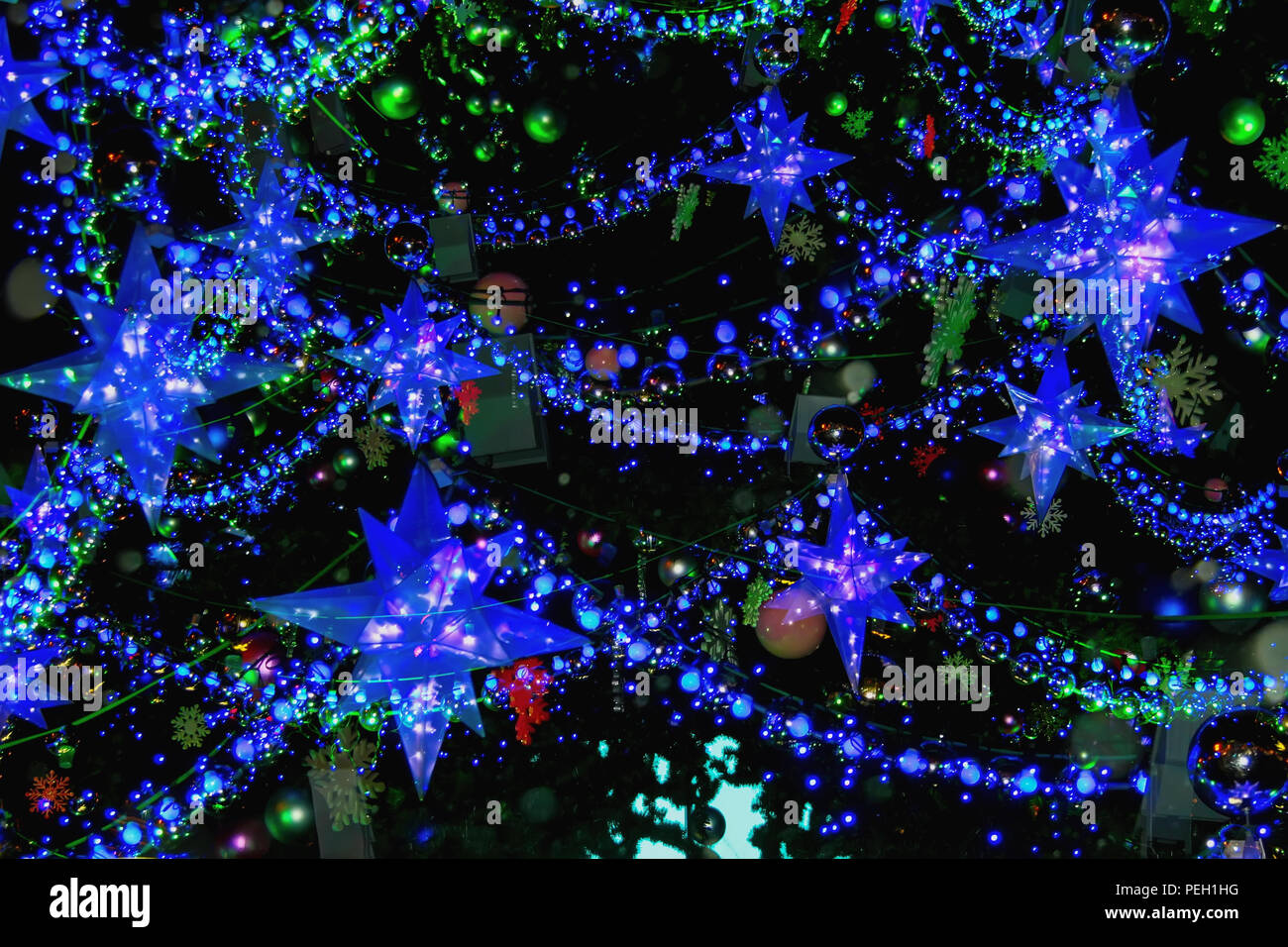 Christmas tree with decorations, christmas stars, snowflakes, balls, garlands. Abstract festive background. Bright blue backdrop for design - Stock Image