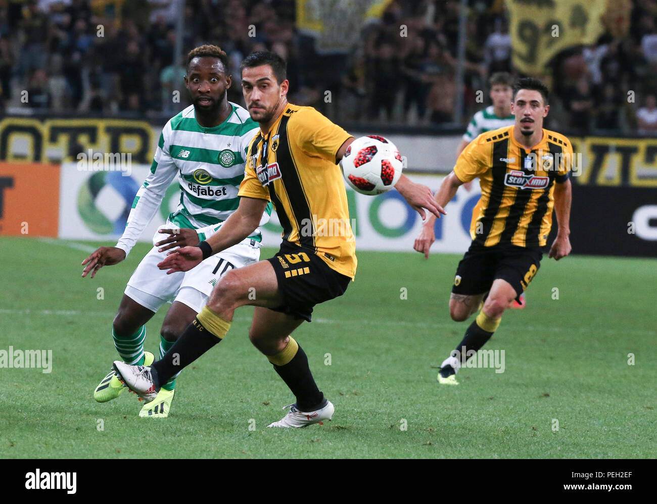 Athens, Greece. 14th Aug, 2018. AEK Athens' Vasileios Lampropoulos (C) vies with Celtic's Moussa Dembele during the third round of Champions League qualifying match in Athens, Greece, Aug. 14, 2018. Credit: Marios Lolos/Xinhua/Alamy Live News - Stock Image