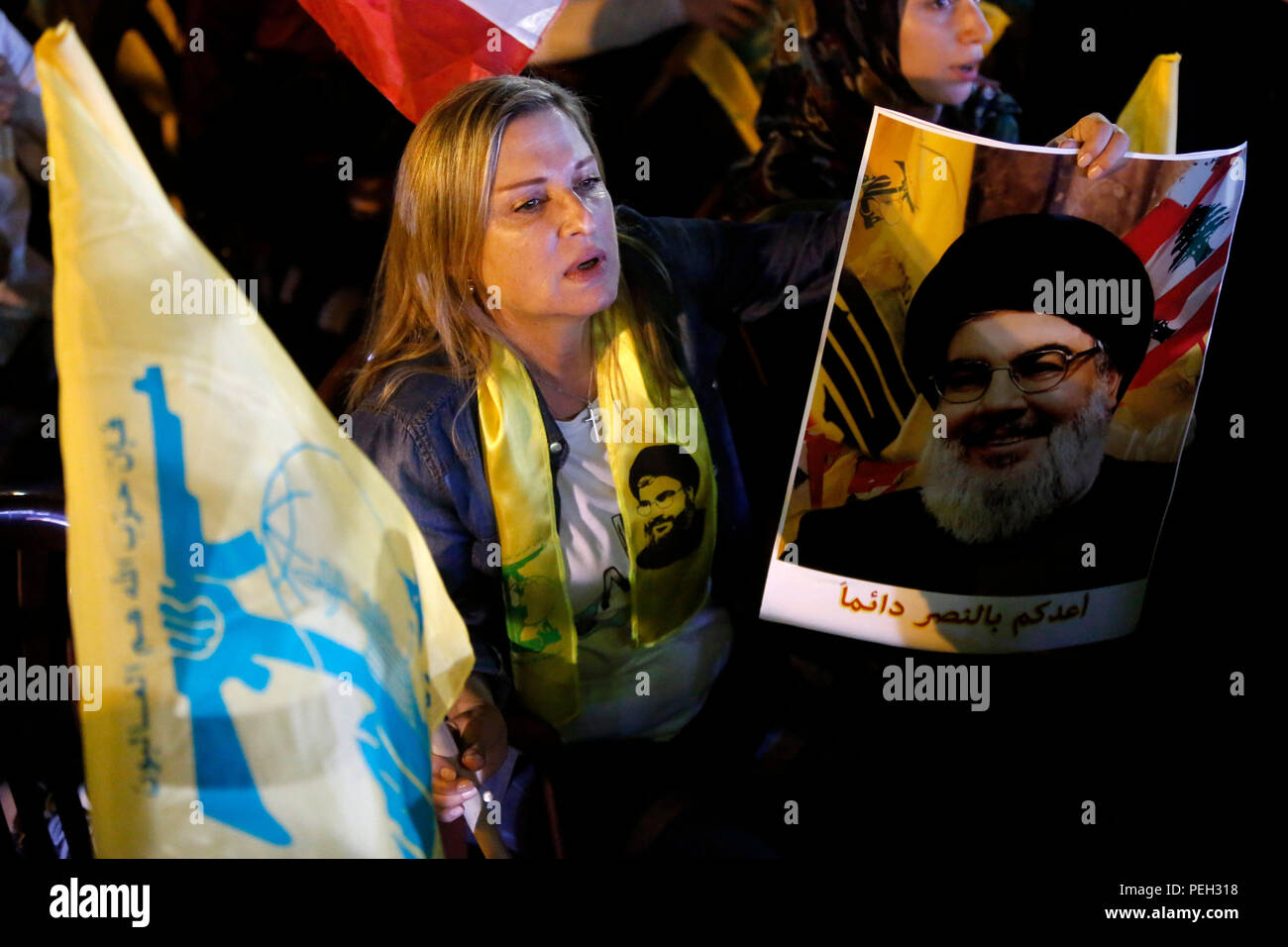 Beirut, Lebanon. 14th Aug, 2018. A woman holds the flag of Hezbollah and the picture of Hezbollah leader Sayyed Hassan Nasrallah during Nasrallah delivering a televised speech in Beirut, Lebanon, Aug. 14, 2018. Hezbollah's leader Sayyed Hassan Nasrallah on Tuesday called on political parties to maintain their negotiation efforts until they reach consensus on cabinet formation in Lebanon. Credit: Bilal Jawich/Xinhua/Alamy Live News - Stock Image
