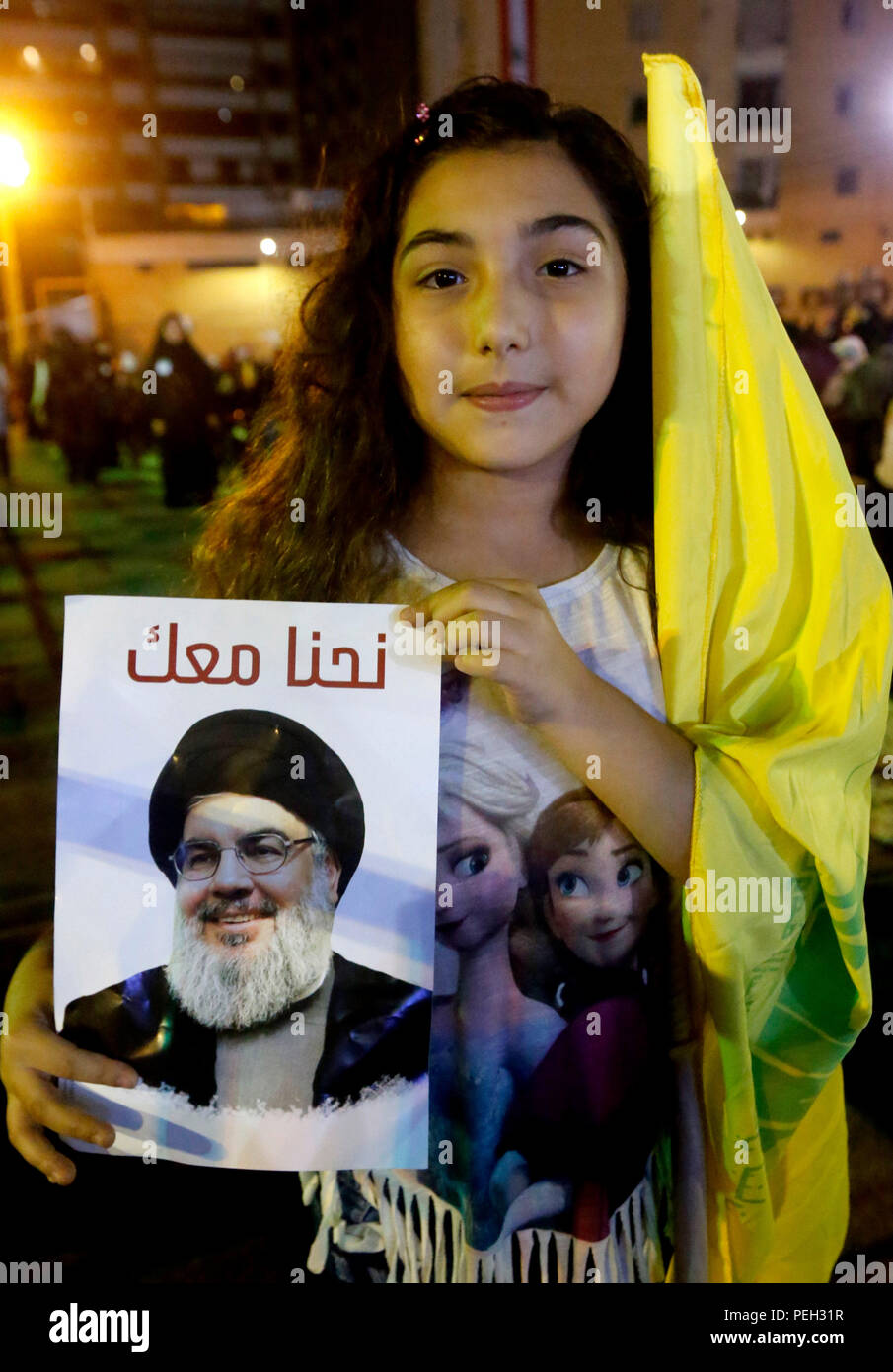 Beirut, Lebanon. 14th Aug, 2018. A girl holds the flag of Hezbollah and the picture of Hezbollah leader Sayyed Hassan Nasrallah during Nasrallah delivering a televised speech in Beirut, Lebanon, Aug. 14, 2018. Hezbollah's leader Sayyed Hassan Nasrallah on Tuesday called on political parties to maintain their negotiation efforts until they reach consensus on cabinet formation in Lebanon. Credit: Bilal Jawich/Xinhua/Alamy Live News - Stock Image