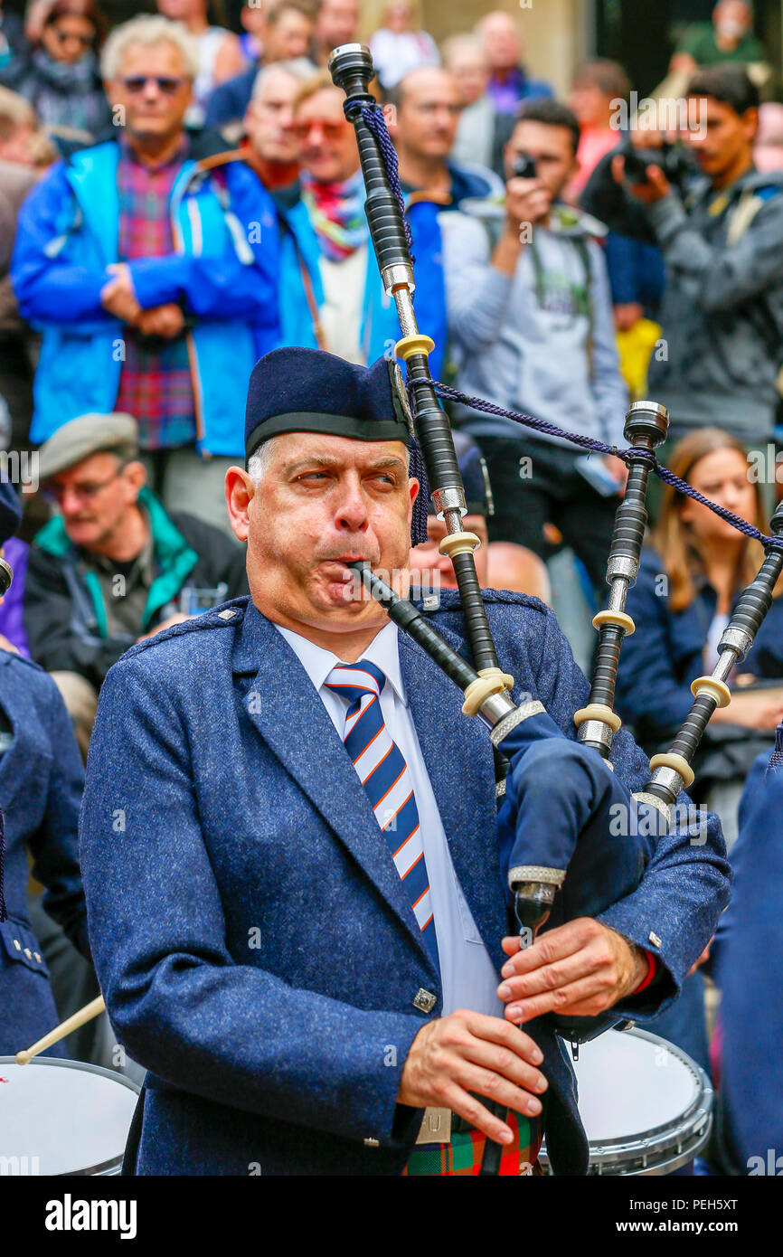Glasgow, UK. 15th Aug 2018. Street performances continue in Buchanan Street, Glasgow with more international pipe bands playing near the Donald Dewar statue to entertain the public for free. The Pipe Band championships conclude on Saturday 18th August at Glasgow Green. Members of the Simon Fraser University Pipe Band from British Columbia, Canada Credit: Findlay/Alamy Live News Stock Photo