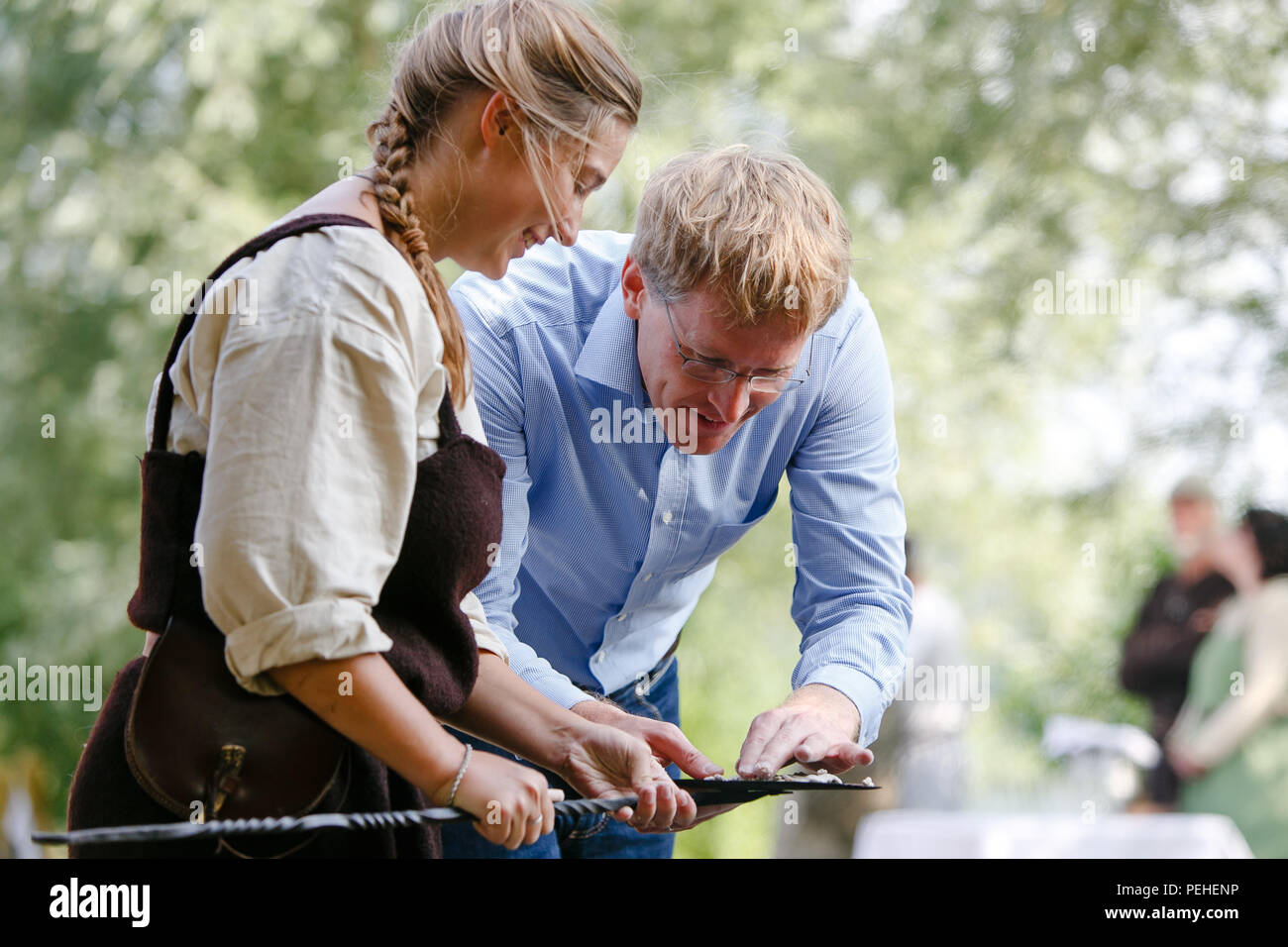 Busdorf, Germany. 16th Aug, 2018. Schleswig-Holstein's Prime Minister Daniel Guenther of the Christian Democratic Union (CDU) bakes bread with an extra. During his four-day summer trip, Guenther visited the Viking Museum Haithabu. Credit: Frank Molter/dpa/Alamy Live News - Stock Image