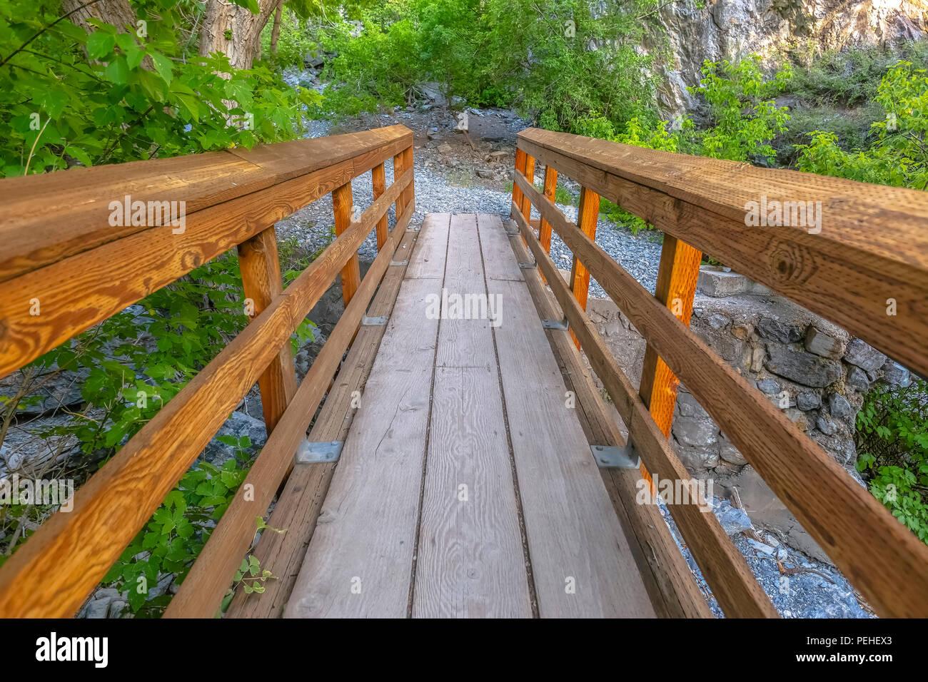 Standing on wooden bridge over rocky stream - Stock Image
