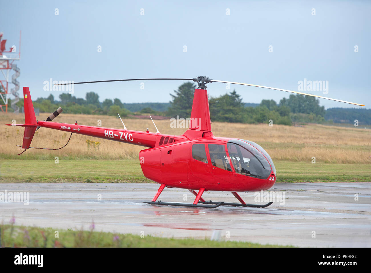 Swiss registered Robinson R66 Light utility and trainer helicopter on the static corner of Inverness Dalcross Airport in the Scottish Highlands. - Stock Image