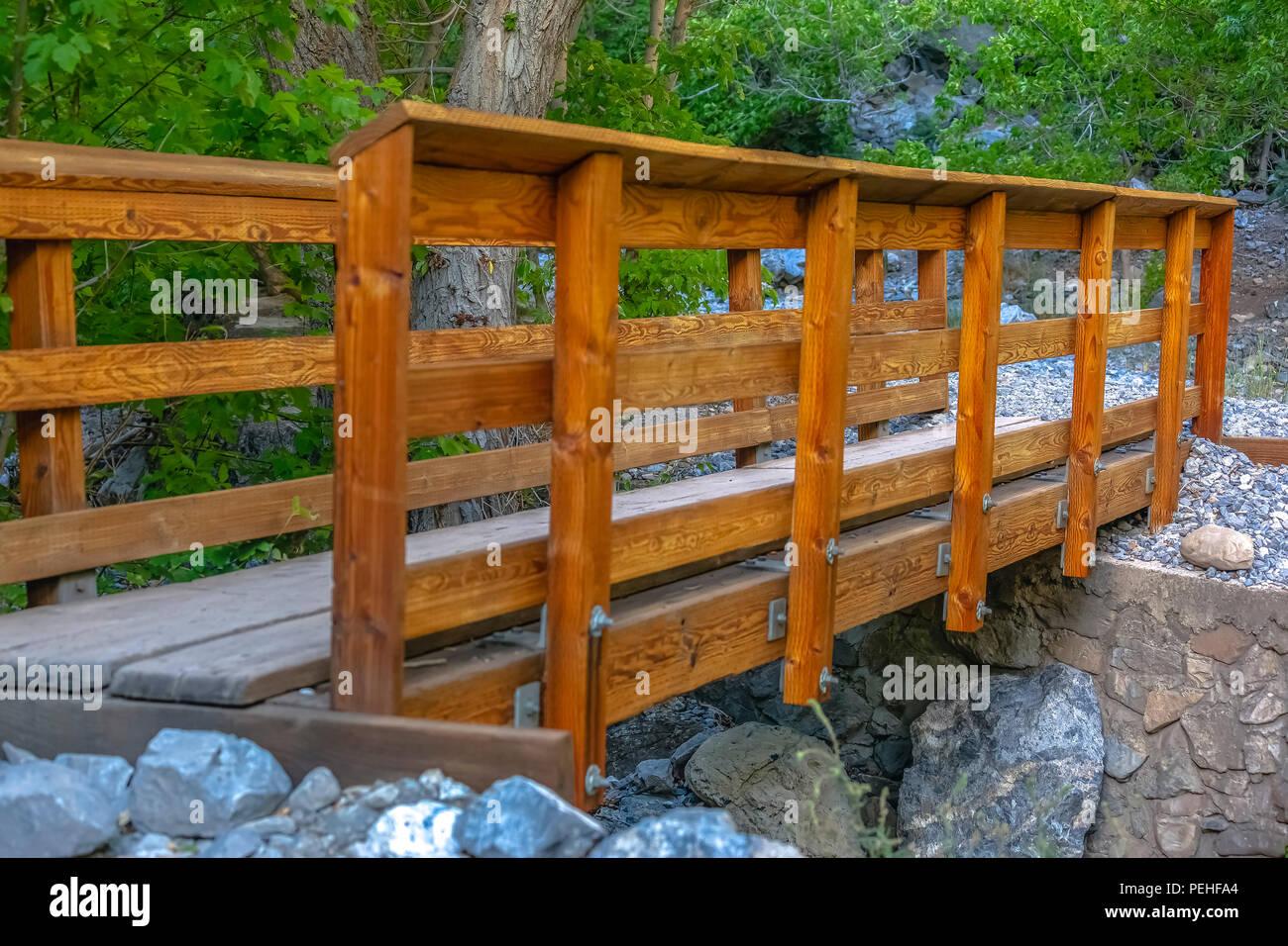 Wooden bridge over a rocky stream - Stock Image