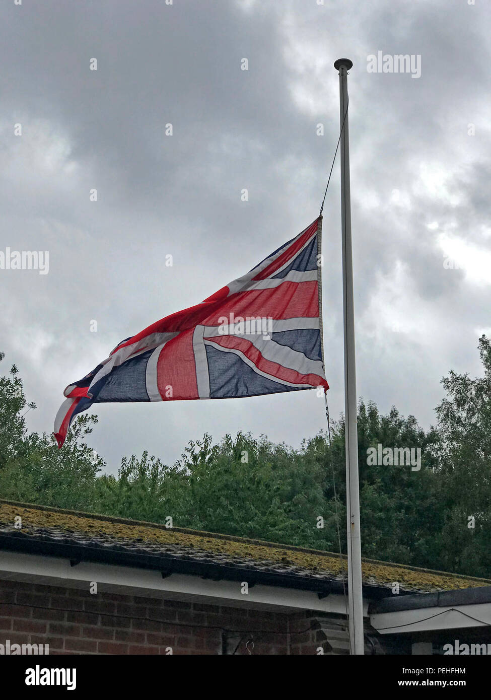 Union Flag, Union Jack at half-mast denoting a death, at Grappenhall & Thelwall British legion, Warrington, Cheshire, North West England, UK - Stock Image
