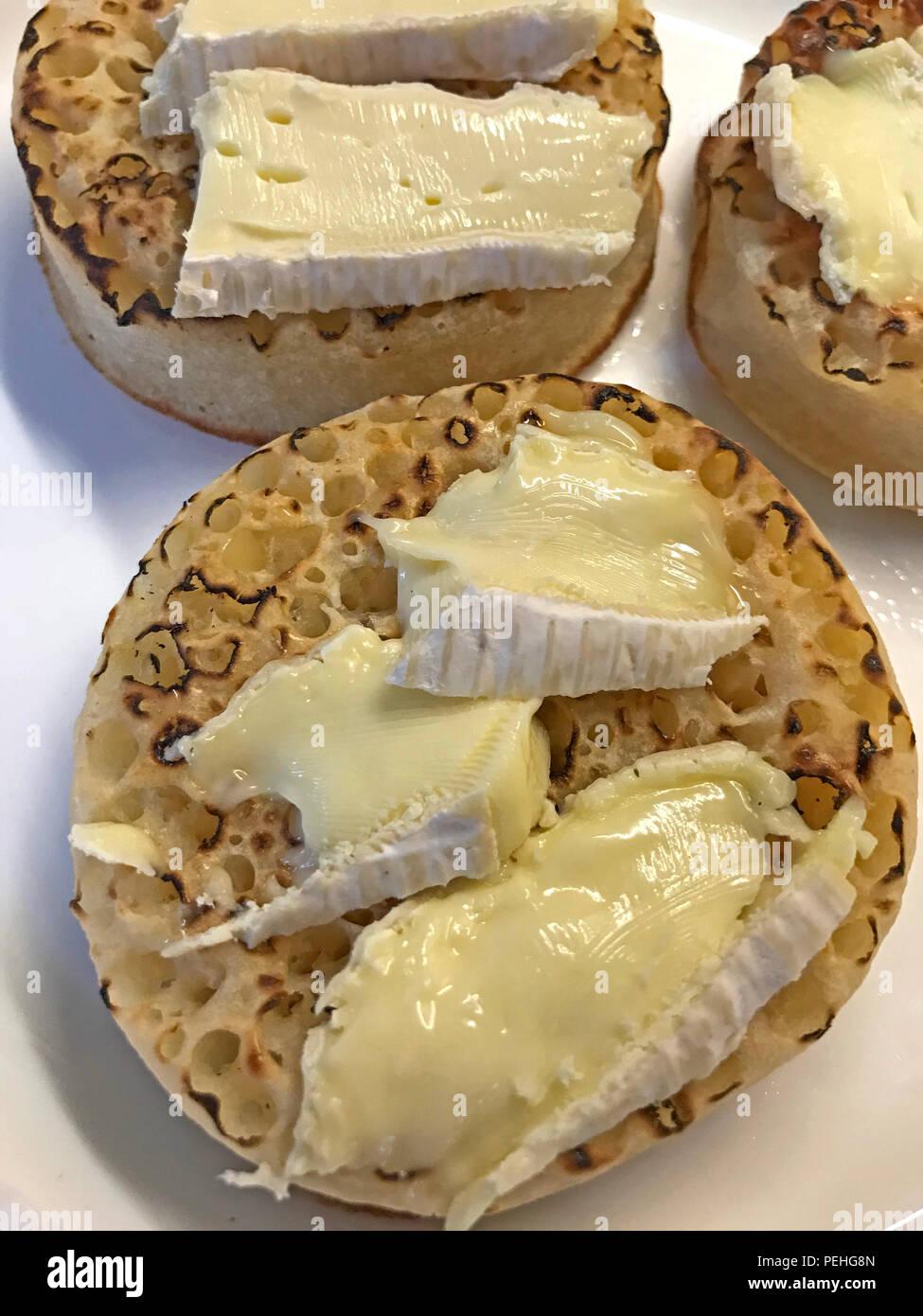 Camembert cheese melting on toasted crumpets - Stock Image