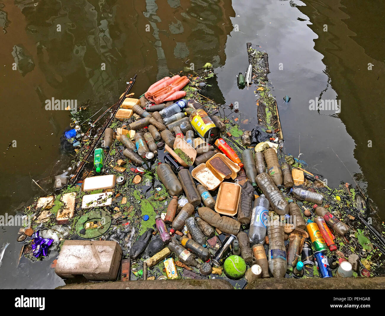 Plastic waste and refuse, in a canal, Castlefields, city centre, Manchester, North West England, UK - Stock Image