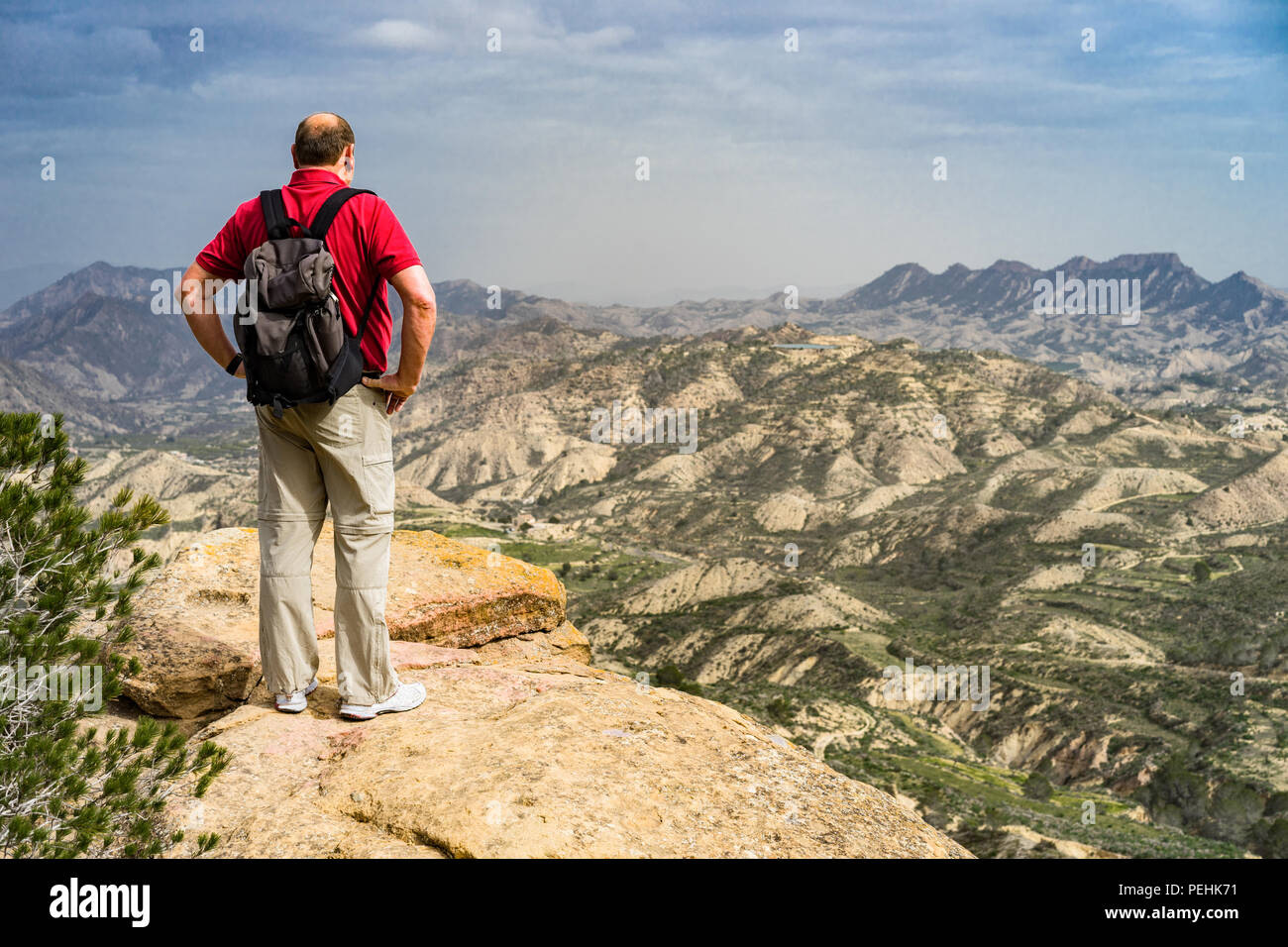 Hiker with red shirt and rucksack stands on a rocky outcrop and views the countryside of Murcia, Spain, looking towards the mountains in the distance. - Stock Image