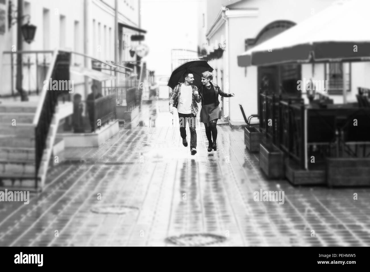 concept of love: loving couple under an umbrella walking down the street of the city.black-and-white photo in retro style - Stock Image