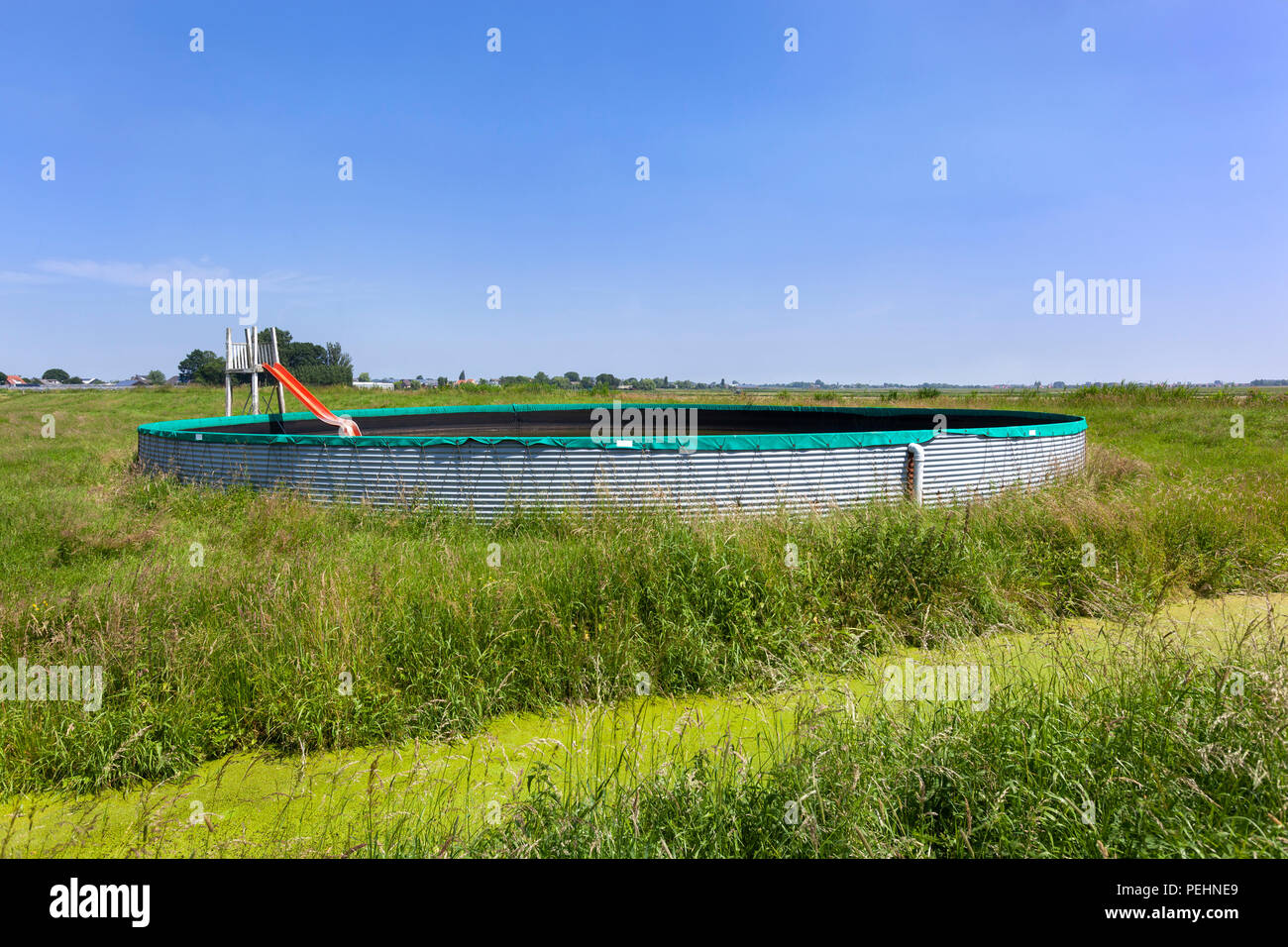 Vintage Swimming Pool Made Of An Water Storage Reservoir With Orange Slide  In The Countryside Pastures In The Netherlands