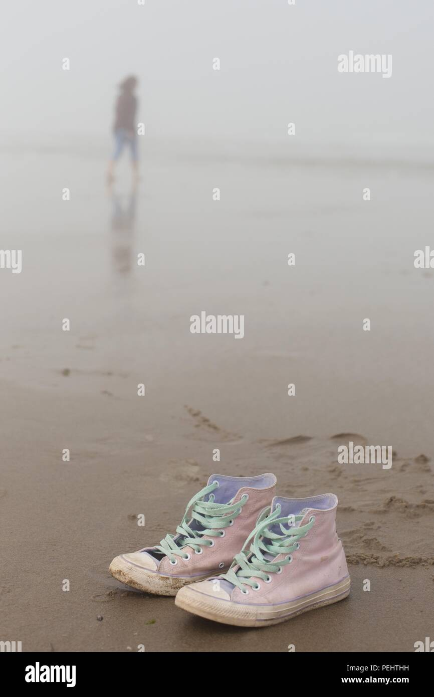 A pair of pink Converse shoes in the foreground and a woman walking in the fog in background at Heceta Beach near Florence, Oregon, USA. - Stock Image