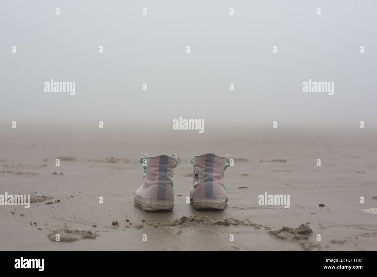 A pair of pink converse shoes on a sandy beach near Florence, Oregon, USA. - Stock Image