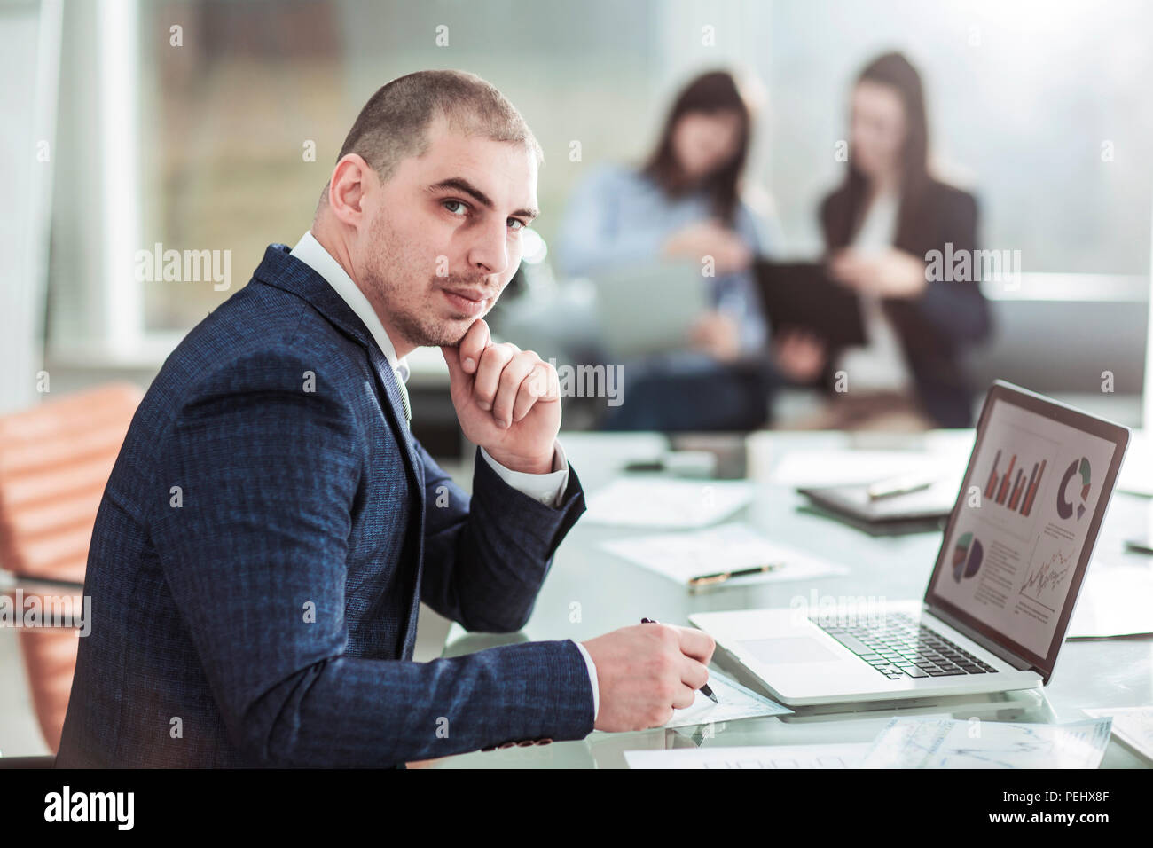senior Manager at the workplace on the background of business team - Stock Image