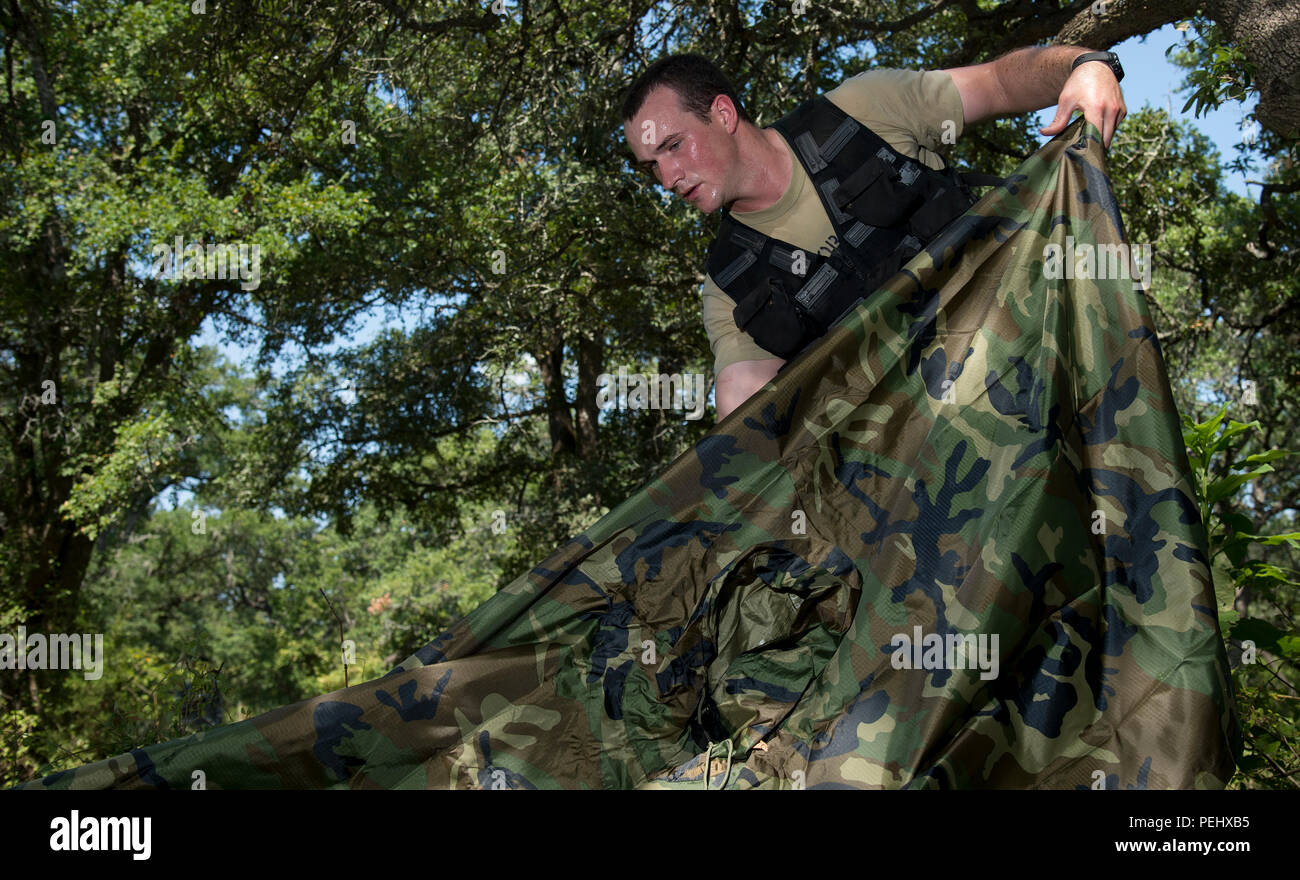 A U.S. Air Force Airman Survival, Evasion, Resistance, Escape candidate prepares to connect two ponchos during a SERE field training and evaluation field exercise at Camp Bullis, Texas, Aug. 17, 2015. SERE candidates are expected to complete the task by themselves, demonstrating the ability to employ evasion and survival tactics and by using available natural cover and resources. (U.S. Air Force photo by Tech. Sgt. Chad Chisholm/Released) - Stock Image
