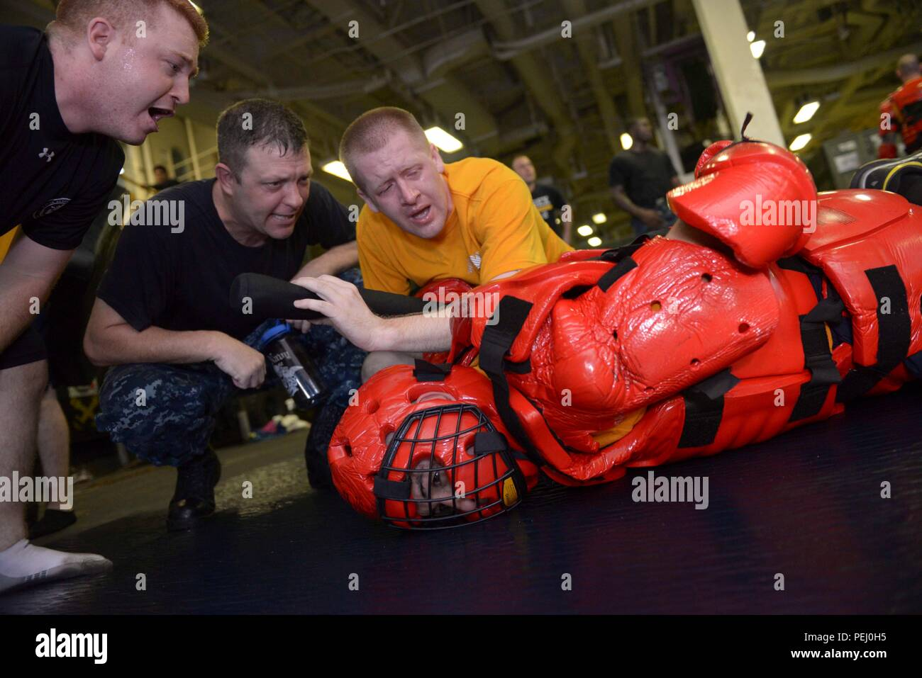"""ARABIAN GULF (Aug. 21, 2015) Legalman 1st Class John Detty uses a Mechanical Advantaged Control Hold (MACH) while under the effects of oleoresin capsicum spray to subdue the """"Redman"""" during a Security Reaction Force (SRF) training course in the upper vehicle storage of Wasp-class amphibious assault ship USS Essex (LHD 2). Essex is the flagship of the Essex Amphibious Ready Group (ARG) and, with the embarked 15th Marine Expeditionary Unit (MEU), is deployed in support of maritime security operations and theater security cooperation efforts in the U.S. 5th Fleet area of operations. (U.S. Navy ph - Stock Image"""