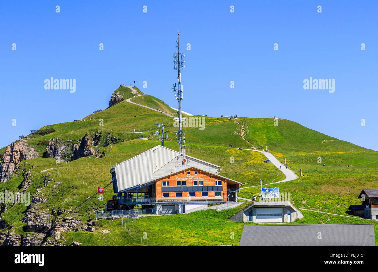 Maennlichen cable car station above Wengen in the Jungfrau region and walking path to the Royal View, Bernese Oberland Switzerland with clear blue sky - Stock Image