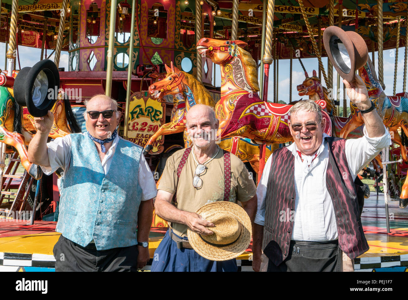 Three fairground workers run the gallopers (merry go round) at a Harris' traditional travelling fair in Wiston Sussex, they wave their hats and smile. - Stock Image