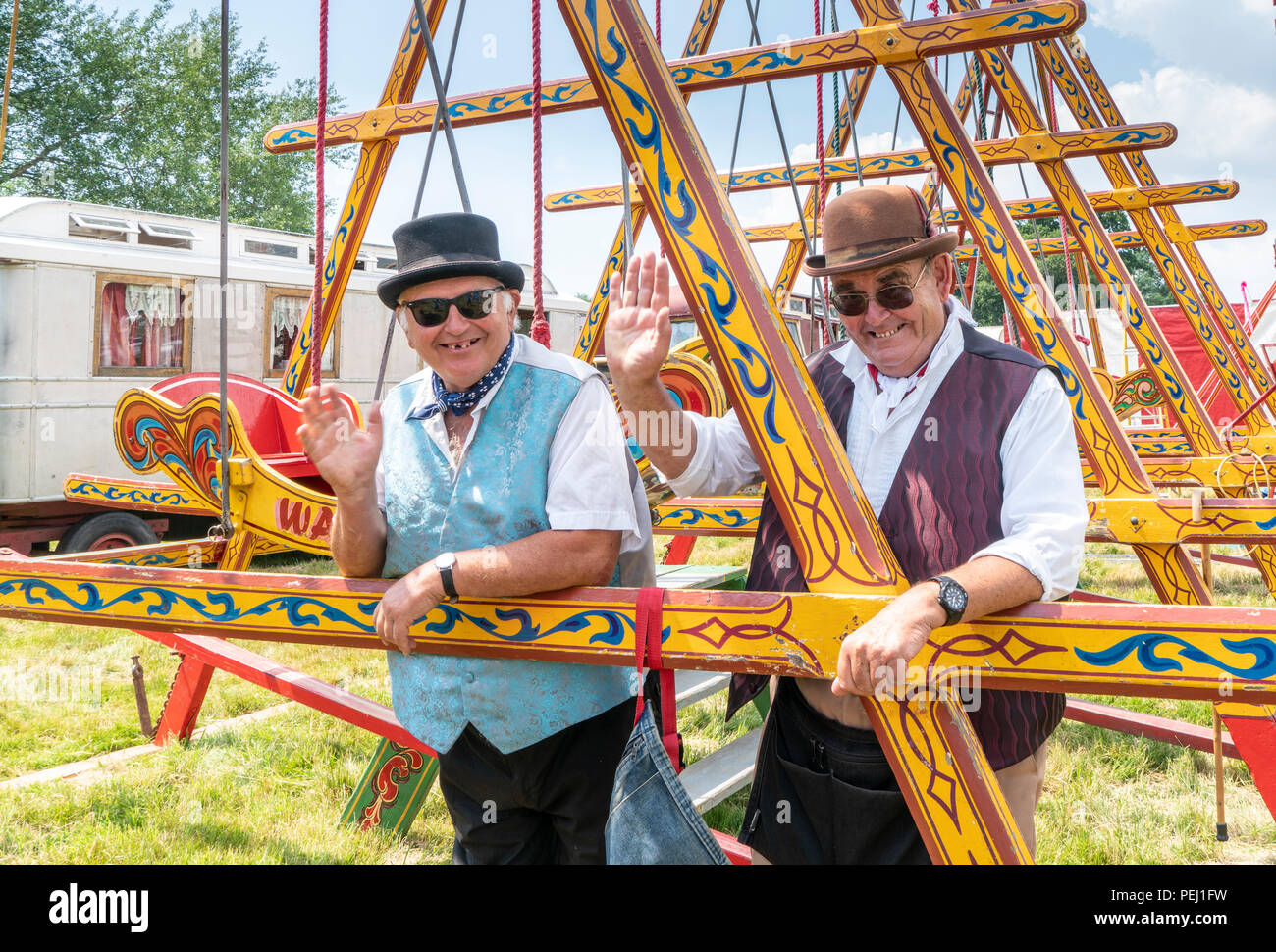 Two workers from the Harris Traditional Vintage Fair wave a greeting from the swing boat ride: they wear vintage waistcoats and bowler hats. - Stock Image
