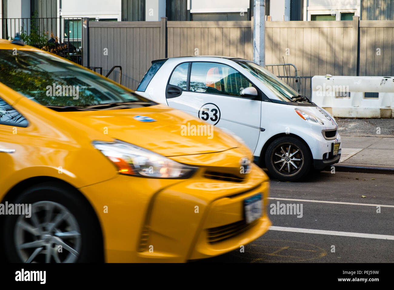 New York yellow taxi passing a Smart Car with Herbie number 53 decal - Stock Image