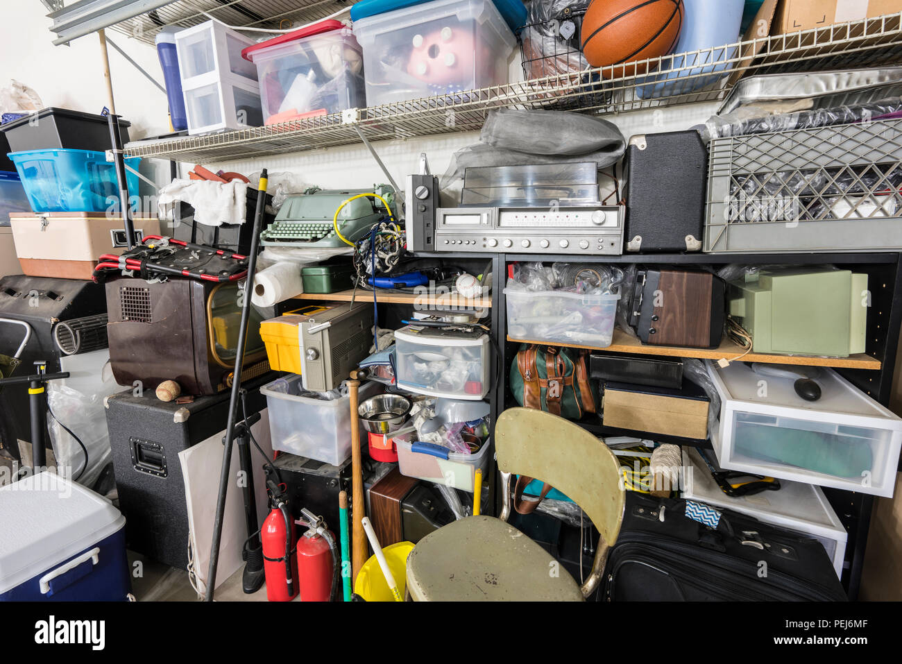 Full shelves of vintage electronics, boxes and sports equipment in typical suburban garage. - Stock Image