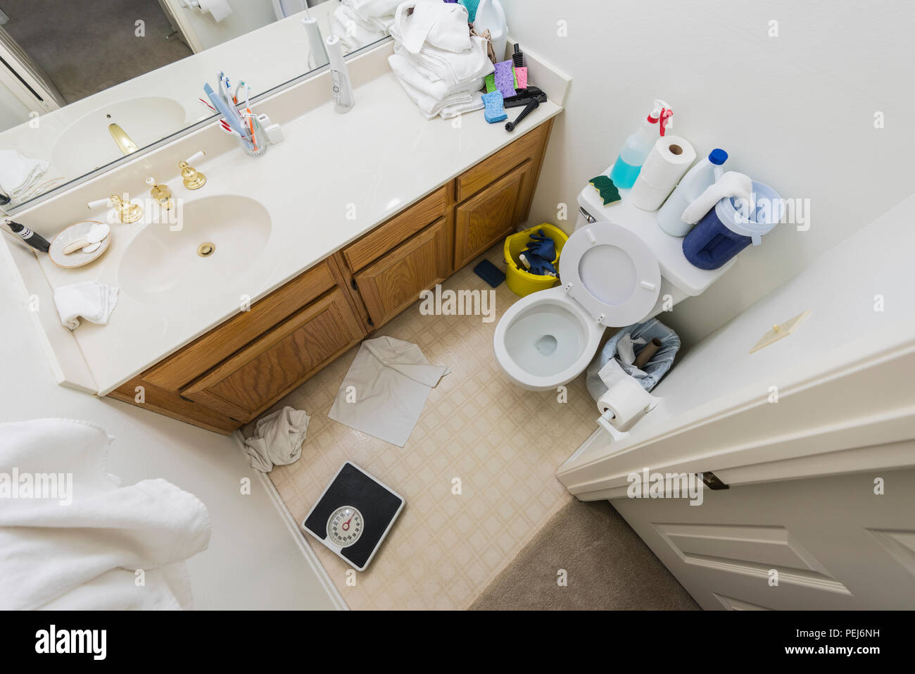 Messy little half bathroom with dirty towels and cleaning clutter. - Stock Image