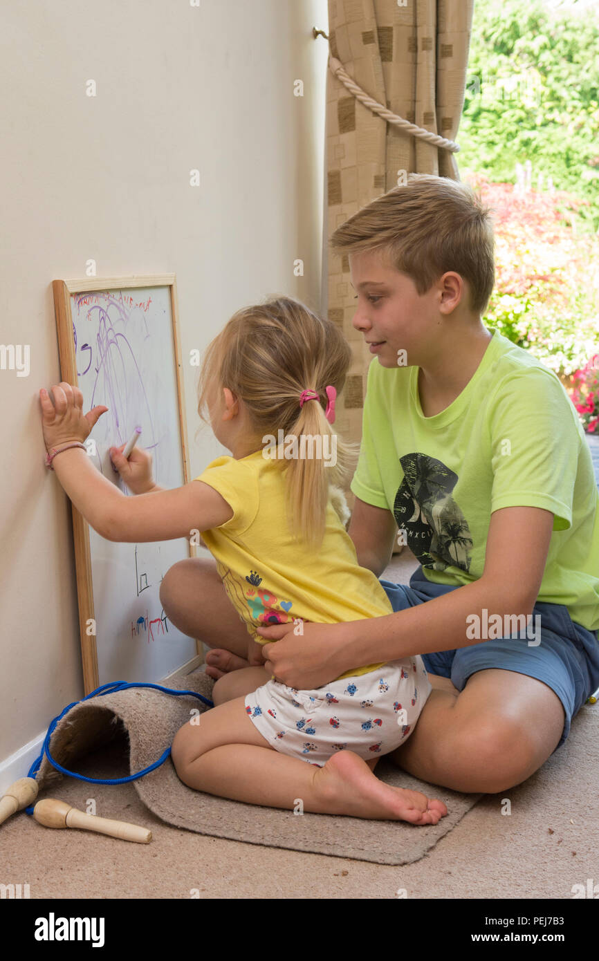 young two year old girl sitting on young twelve year old brother's lap, drawing with coloured pen on white board, being artistic, - Stock Image