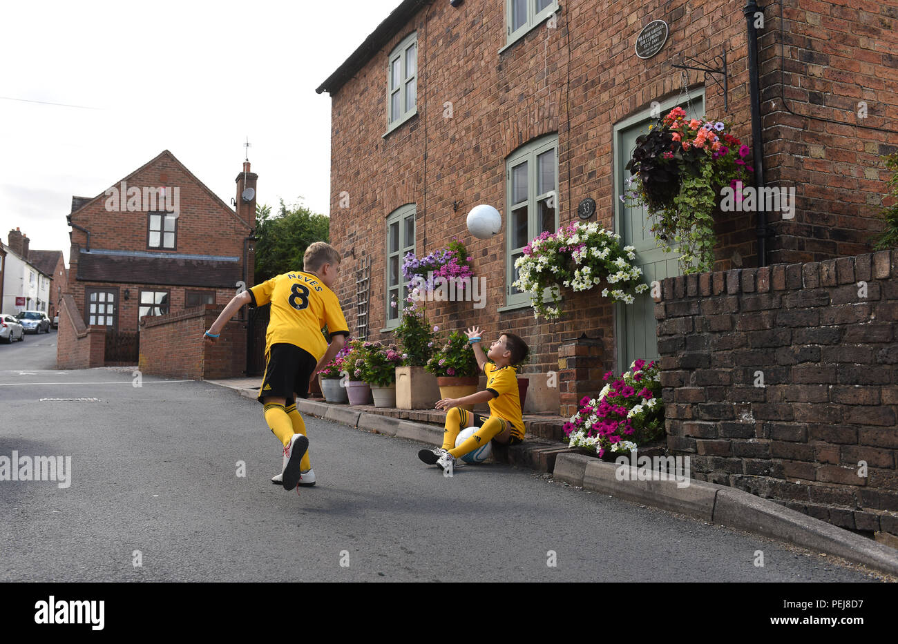Boys in Wolverhampton Wanderers FC replica kits playing football outside the birthplace of Wolves and England footballing legend Billy Wright in Ironb Stock Photo