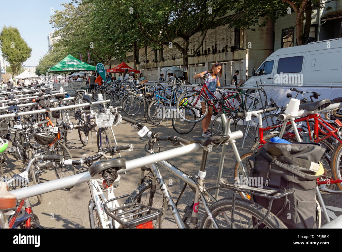 Bicycles and female worker in a free and secure Bicycle Valet  bicycle parking lot, Vancouver, BC, Canada - Stock Image