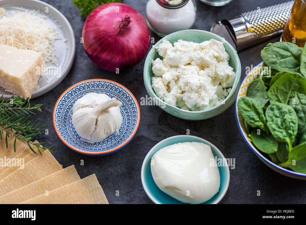 Ingredients for Vegetarian Spinach and Ricotta Lasagna, top view, dark background - Stock Image