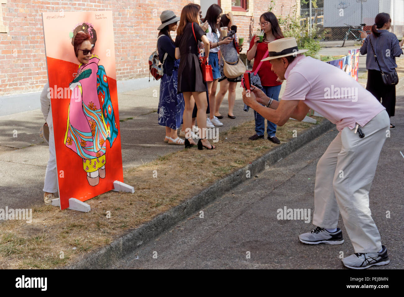 Man photographing his wife posing in a head in the hole cutout at the 2018 Powell Street Festival in Japantown, Vancouver, BC, Canada - Stock Image
