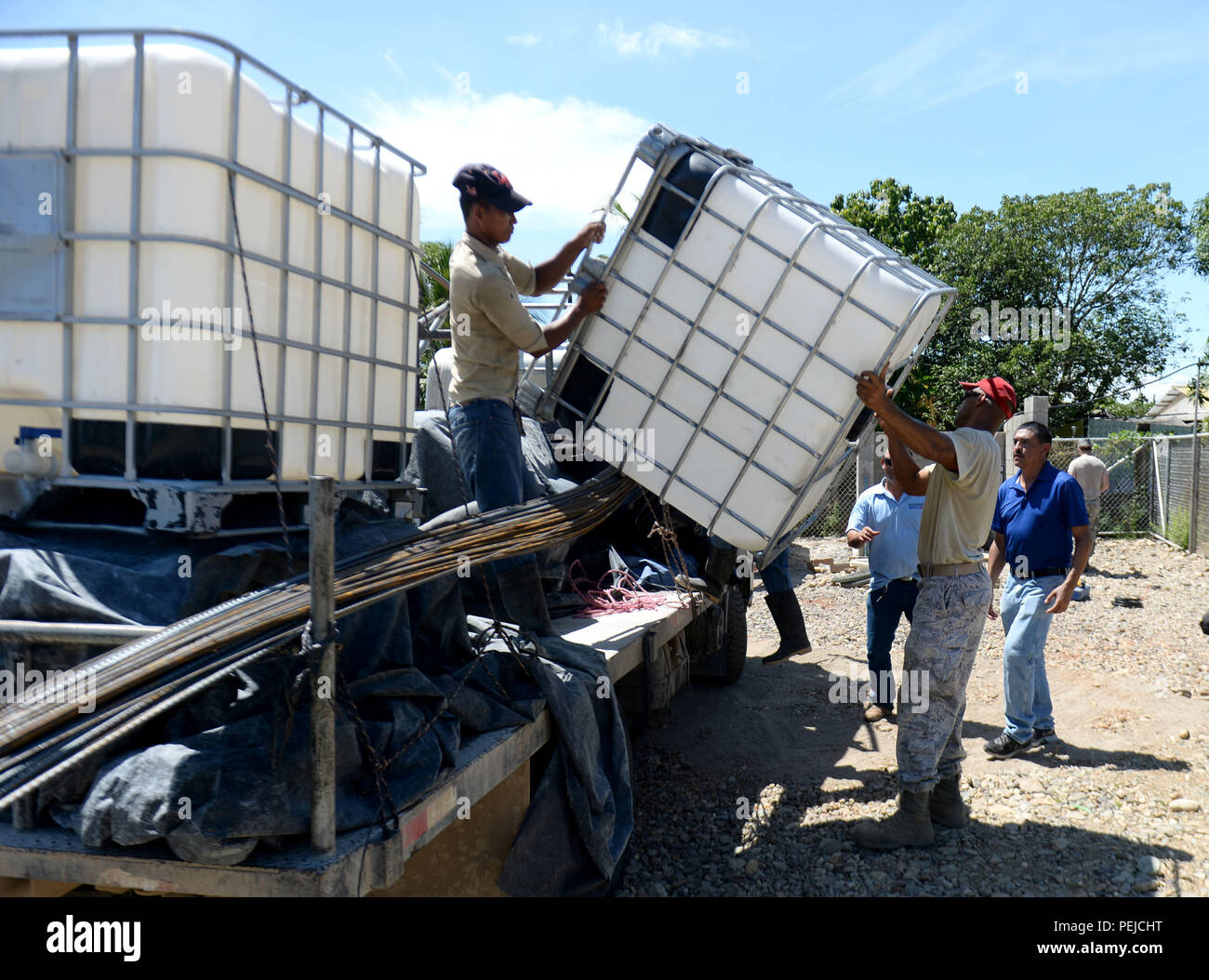 U.S. Air Force Tech. Sgt. Elton Vance, 823rd Expeditionary RED HORSE Squadron well-drilling craftsman, out of Hurlburt Field, Fla., helps unload one of two 250-gallon tanks at the well site in Honduras Aguan, Honduras, Aug. 27, 2015. The tanks were donated to both this well site and the well site in Brisas del Mar, Honduras, in order to give resident a temporary storage location for their water. Both wells were drilled as part of the New Horizons Honduras 2015 training exercise. New Horizons was launched in the 1980s and is an annual joint humanitarian assistance exercise that U.S. Southern Co - Stock Image