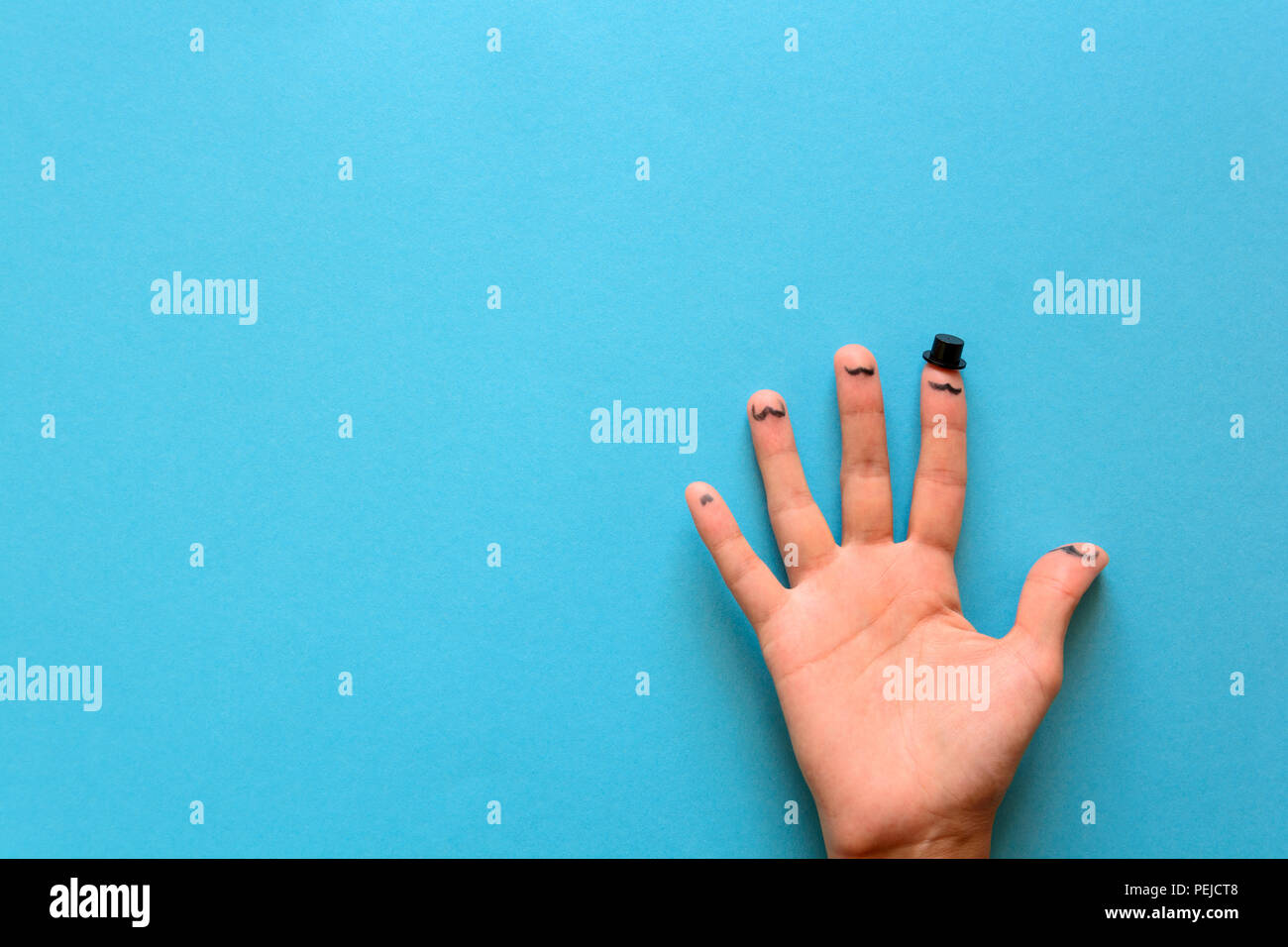 Fingers with a mustache and cylinder on blue paper background. Movember concept. Top view. Flat lay. - Stock Image