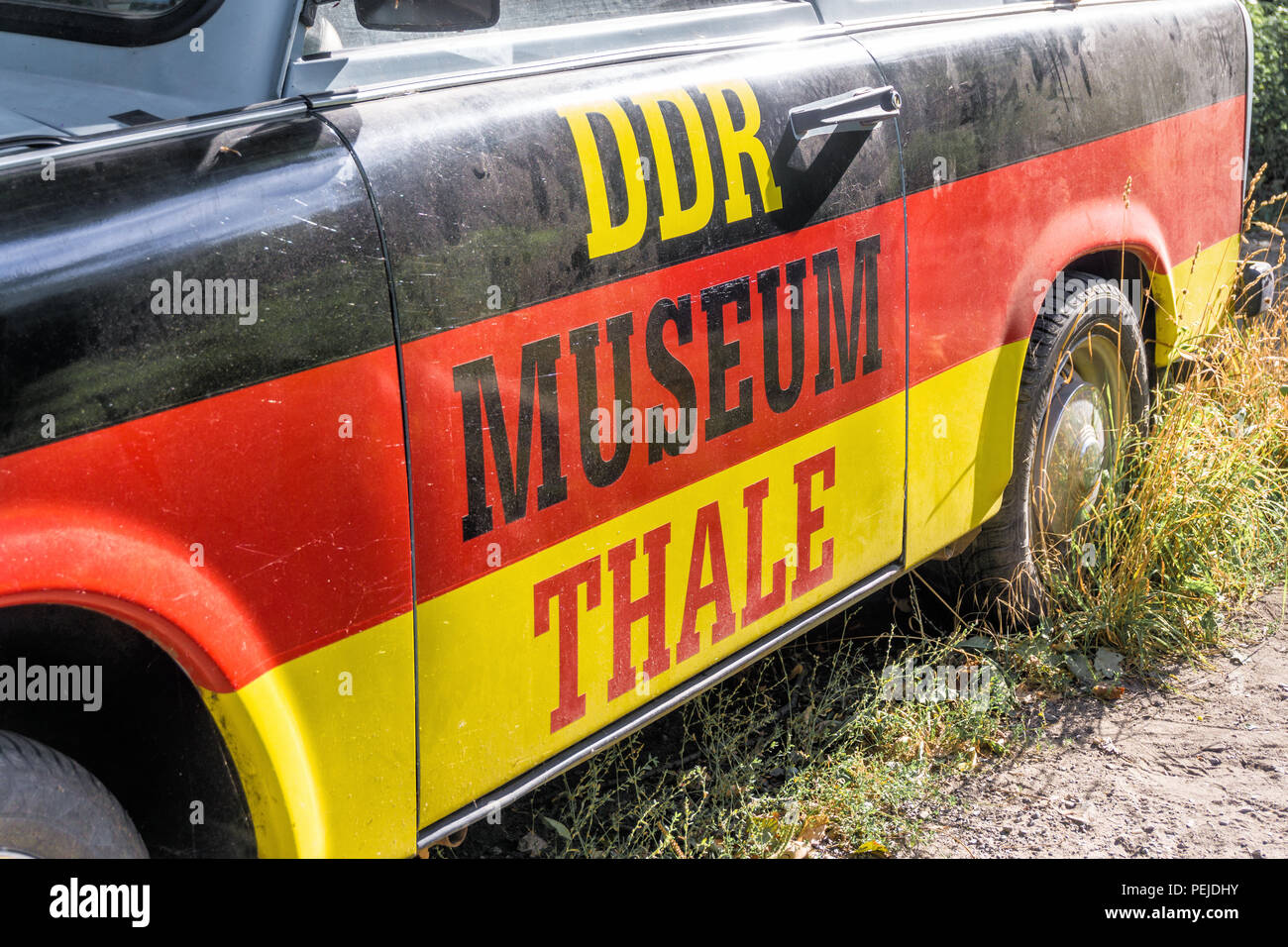 Thale, Saxony-Anhalt, Germany, July 12, 2018: Old dirty ugly Trabant with black-red-gold paint as advertisement for the GDR Museum Thale, closeup. - Stock Image