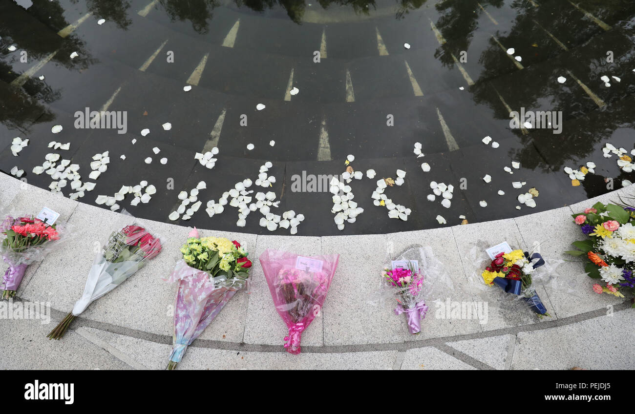 White Rose petals are thrown into a pond at the Omagh Memorial garden by people who attended the ceremony for victims of the car bomb on Market Street on the 15th August 1998. - Stock Image