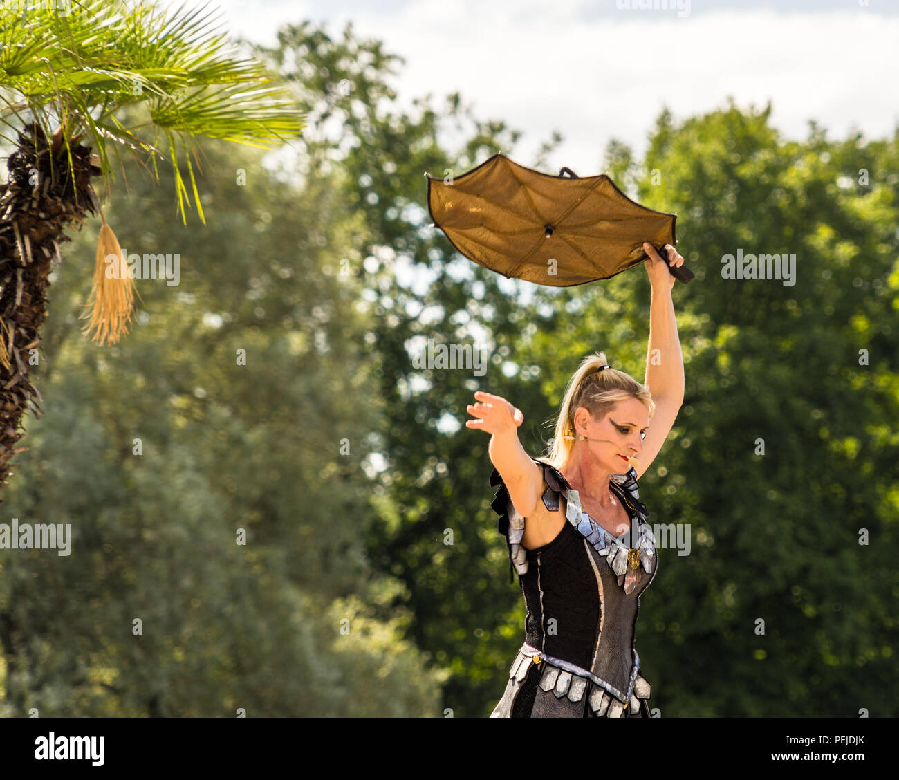 Hanover, Lower Saxony, July 5, 2018: Tightrope walker in black dress with a yellow umbrella for balancing at the Maschsee Festival in Hanover. - Stock Image