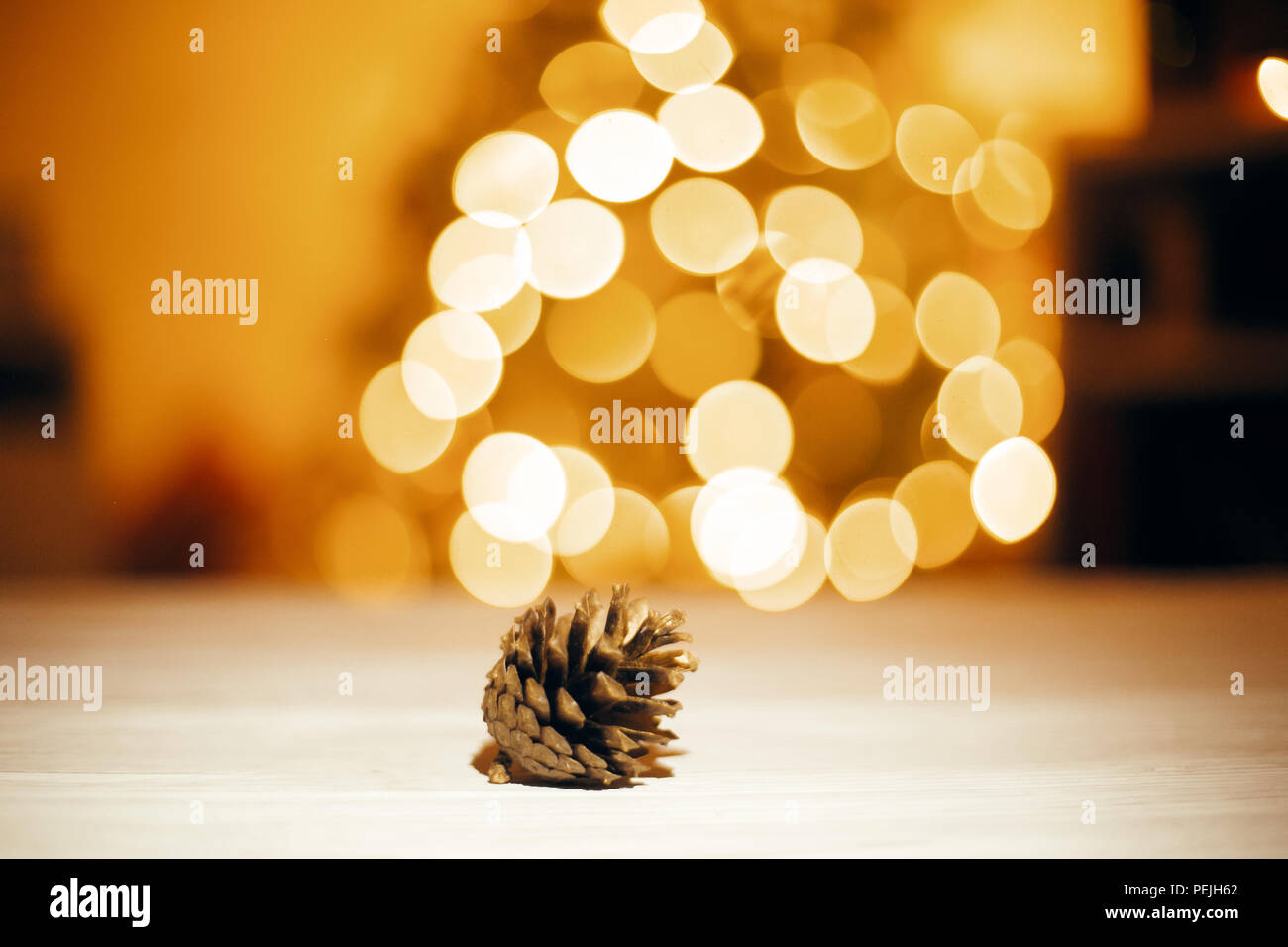 golden pine cone on wooden table on background of christmas tree in festive lights space for text merry christmas and happy new year concept