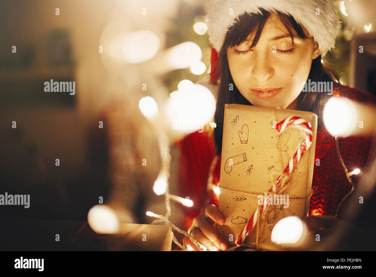fbb37f19ffe4a christmas magic moments. girl in santa hat and red sweater holding christmas  present in lights in evening festive room at tree illumination. merry chr
